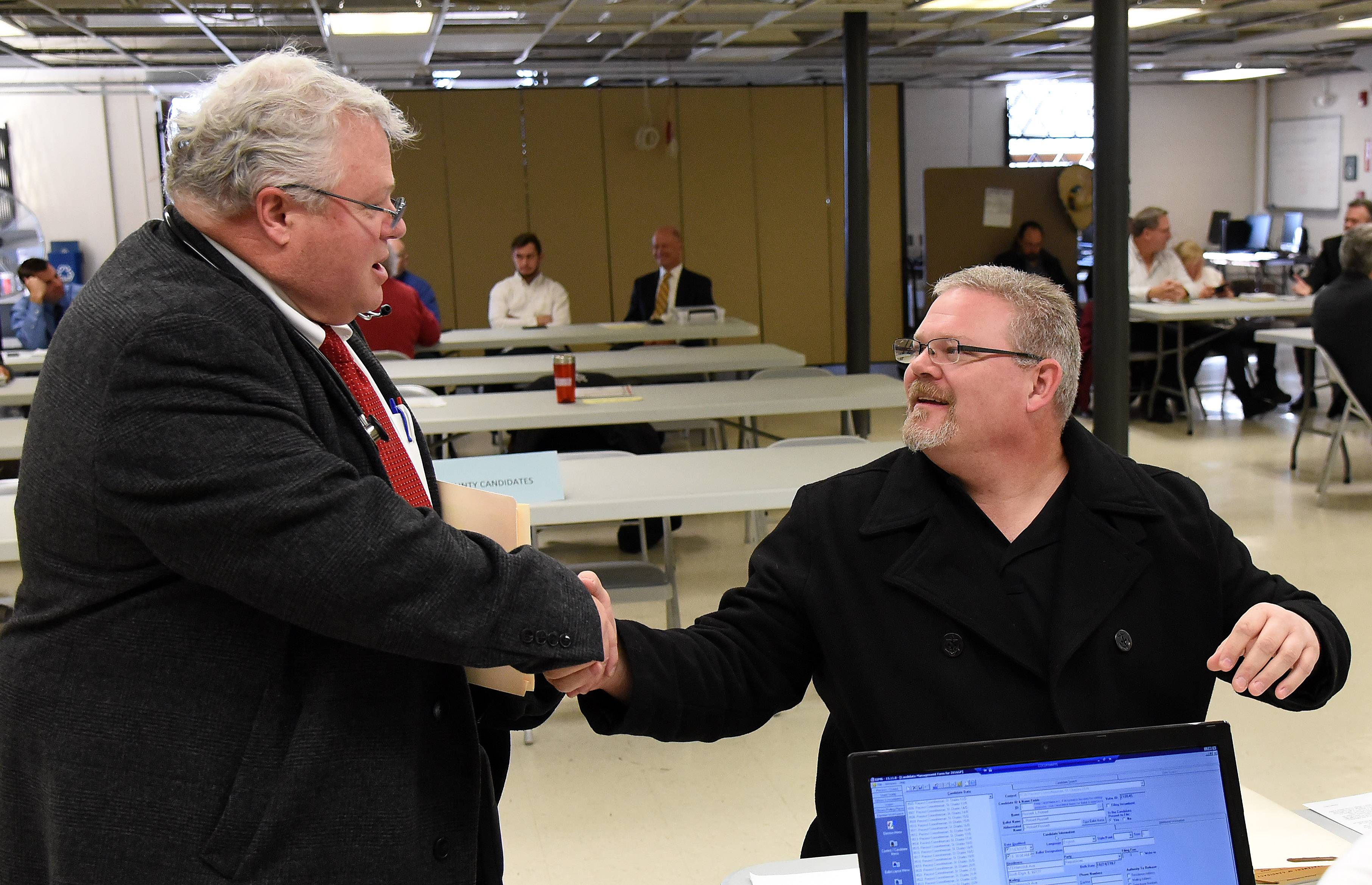 They have a contentious history, but on Monday Republican primary challenger Dr. Bob Tiballi, left, and Kane County Coroner Rob Russell shake hands on the first day of candidate filing for the March primary.