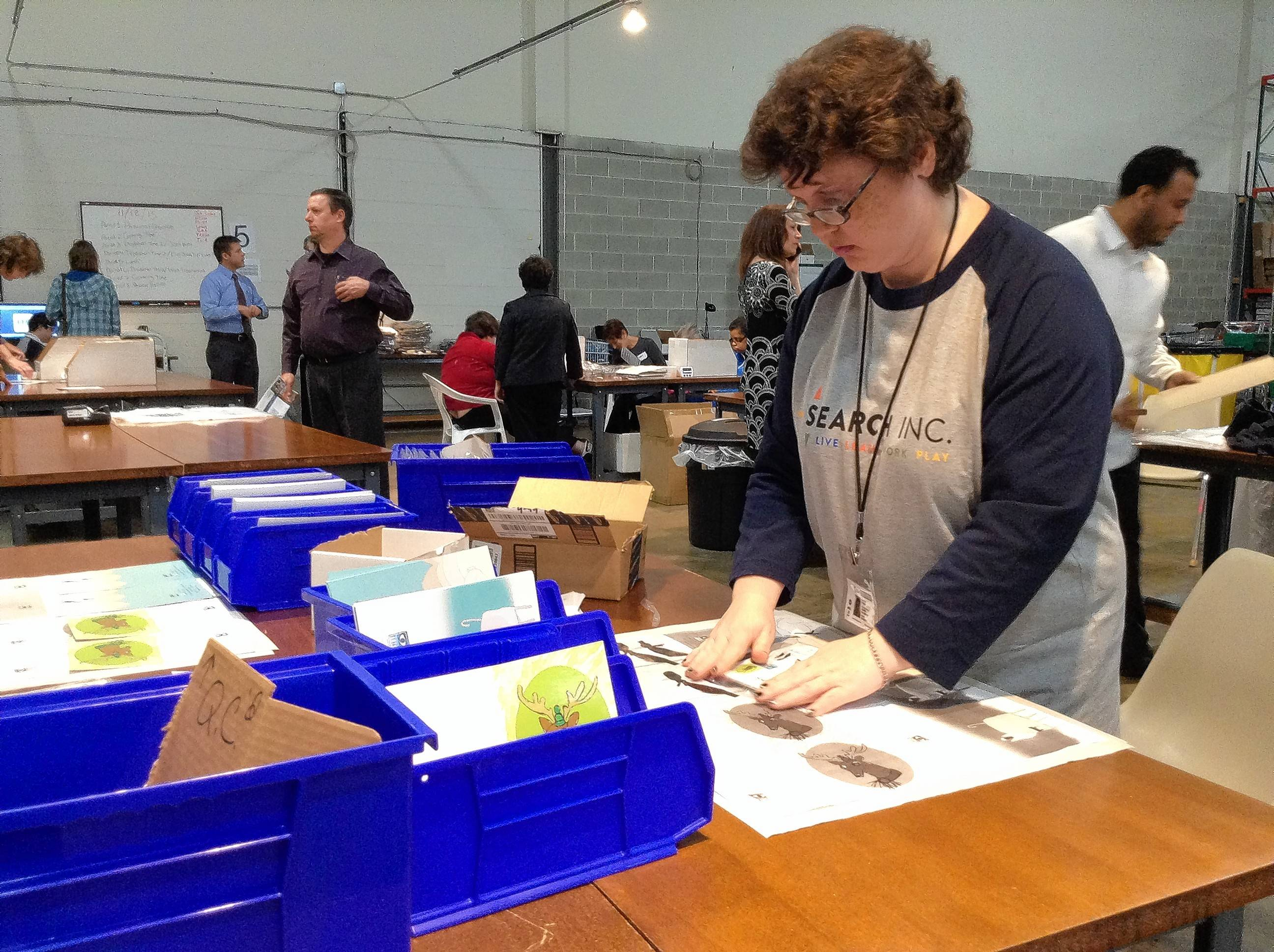 Alison Palsgrove, 42, of Mount Prospect, works on folding and packaging holiday greeting cards that will be sold at the Chicago retail store of Planet Access Co., which relocated its warehouse from Waukegan to Des Plaines.