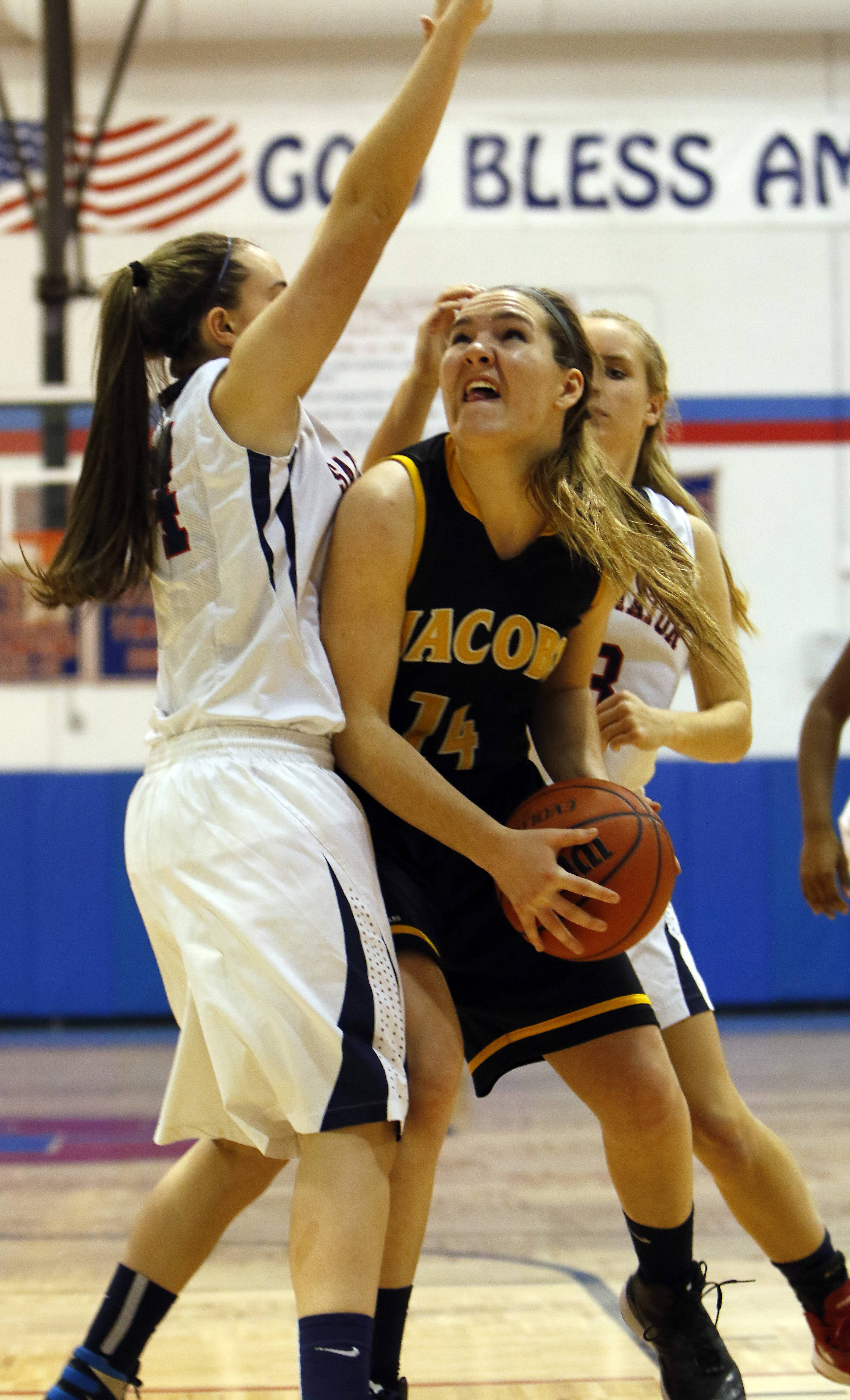 Jacobs' Maggie Grady (14) goes up strong against St. Viator's Haley Robinson, (24) during girls basketball action at Dundee-Crown Friday in Carpentersville.