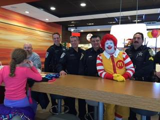 "Arlington Heights police pose with Ronald McDonald during their launch of the department's ""Befriend a Badge"" program."