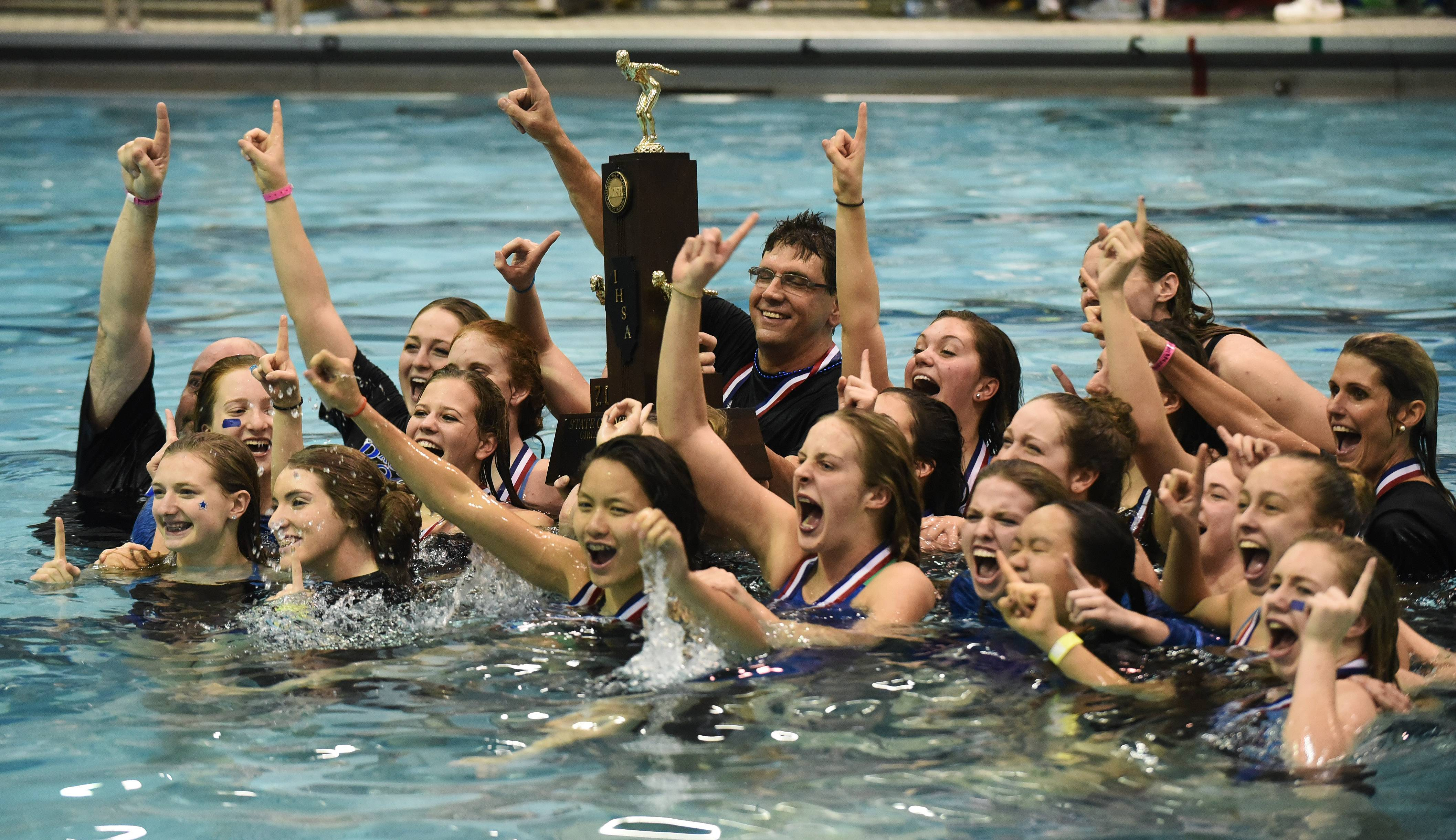 Rosary swimmers celebrate in the pool with their first-place trophy following the girls state swimming finals at New Trier High School in Winnetka Saturday.