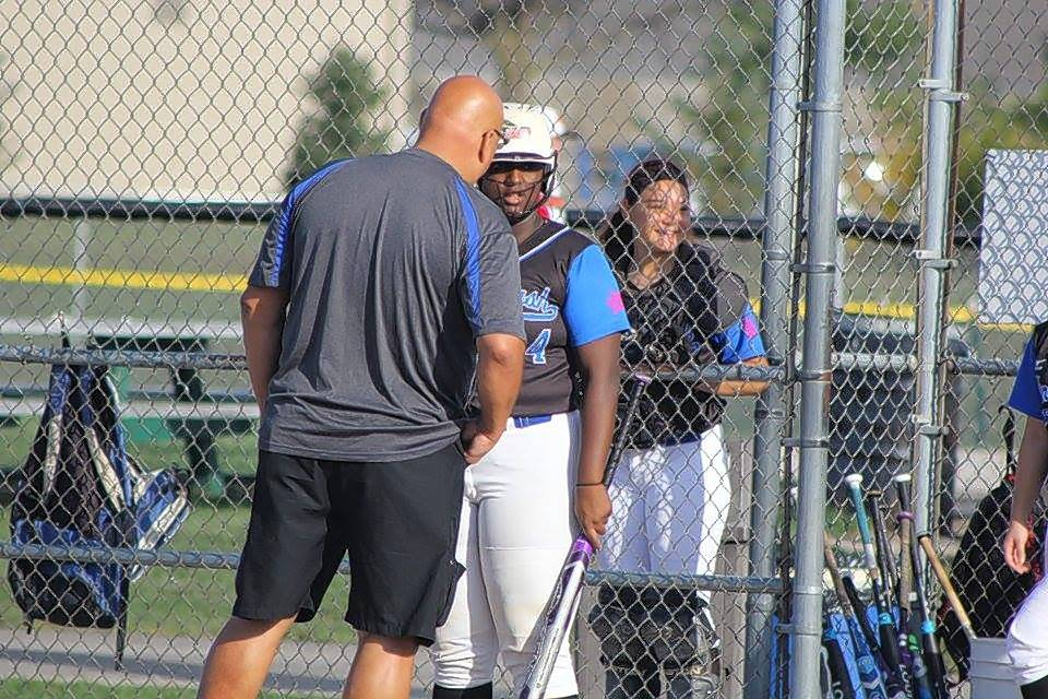 Illinois Bash coach Jim Goranson has a midgame chat with Conant High School senior Dream Aaron, whose softball prowess has earned her a full college scholarship in Florida.