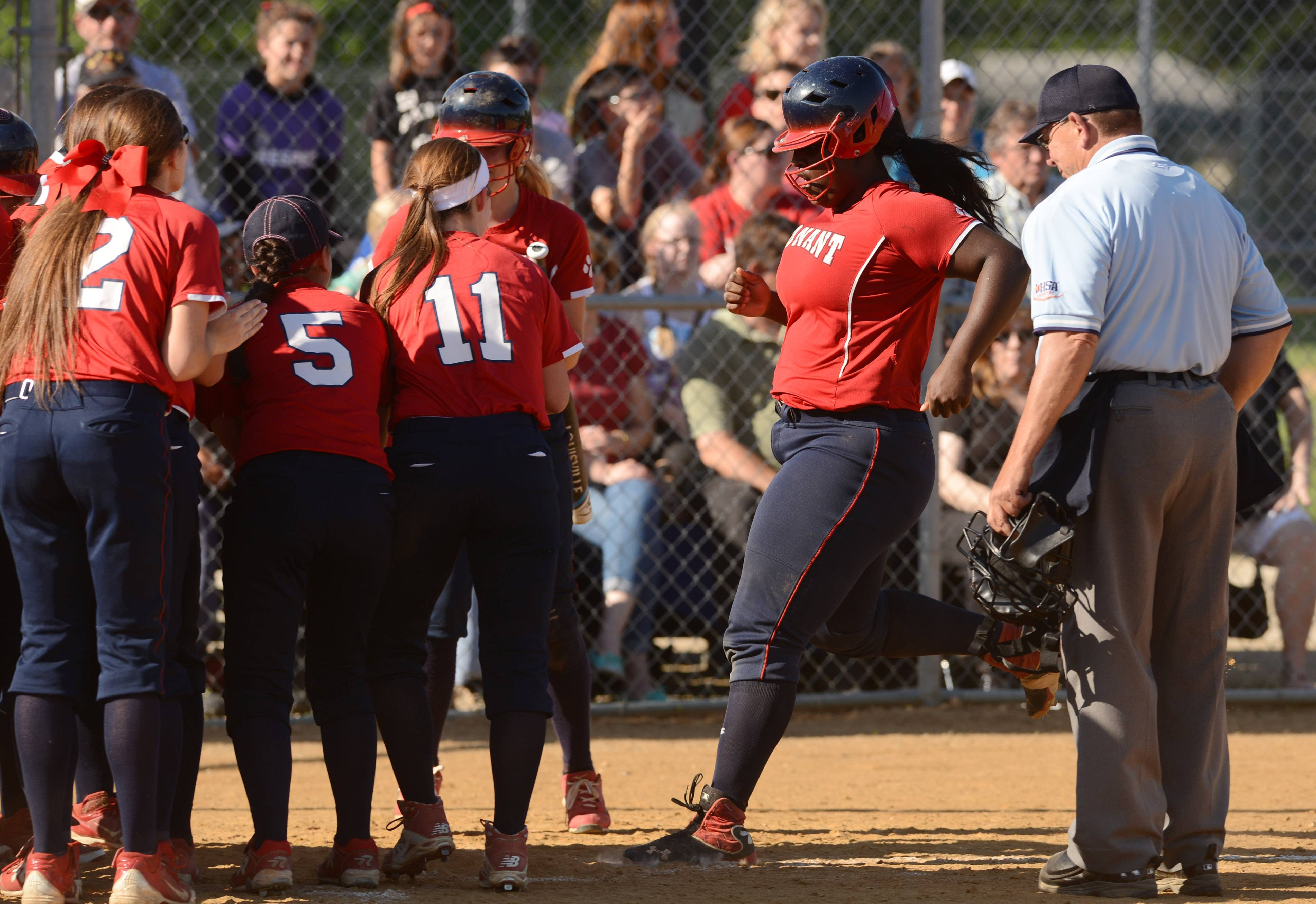 Conant's Dream Aaron, right, is greeted at the plate by her teammates after hitting a home run last season. Despite adversity including homelessness and her mother's imprisonment, Dream has earned a full scholarship to college.