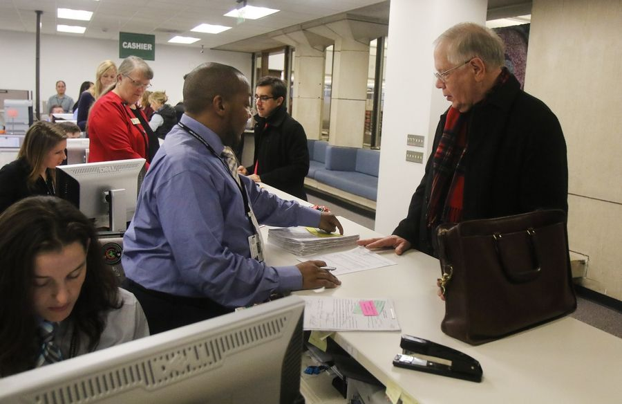 Lake County Coroner Thomas Rudd, right, talks to Lake County clerk's office staff member Todd Govain about his filing papers Monday in Waukegan. About 20 candidates waited for the doors to open at 8:30 a.m. with hopes of their names appearing first on the ballot.