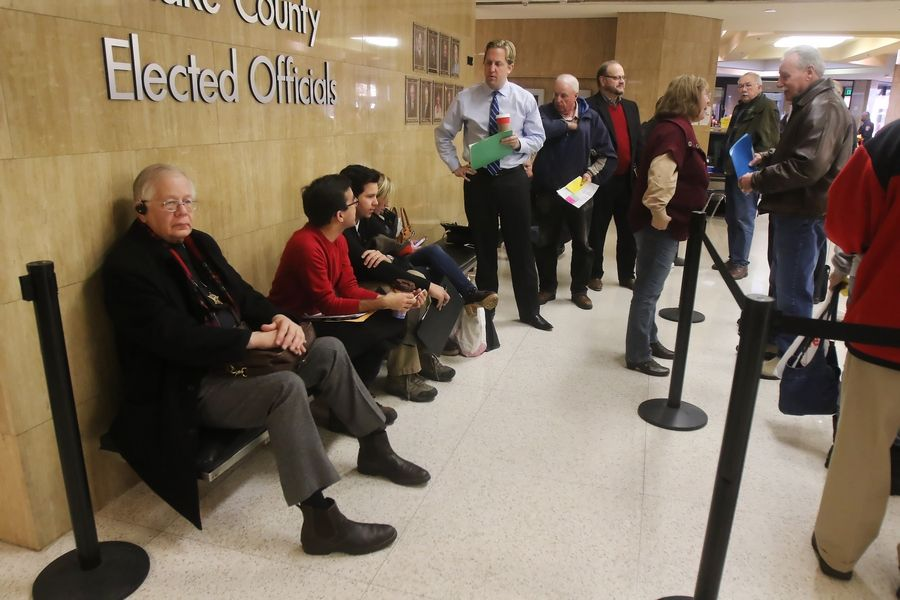 Lake County Coroner Thomas A. Rudd, left, is first in line on the first day of filing for candidates Monday at the Lake County clerk's office in Waukegan. About 20 candidates waited for the doors to open at 8:30 a.m. with hopes of their name appearing first on the ballot.