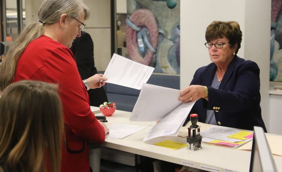 Lake County Board member Carol Calabresa, right, hands filing papers to Lake County Clerk staff member Mary Ann Potter on the first day of filing for candidates Monday. About 20 candidates waited for the doors to open at 8:30 a.m. with hopes of their name appearing first on the ballot.
