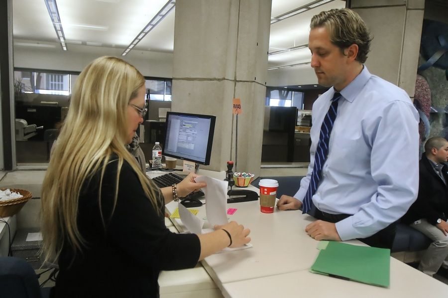 Lake County Board Chairman Aaron Lawlor, right, hands filing papers to Lake County Clerk staff member Mary Peavey on the first day of filing for candidates Monday. About 20 candidates waited for the doors to open at 8:30 a.m. with hopes of their name appearing first on the ballot.