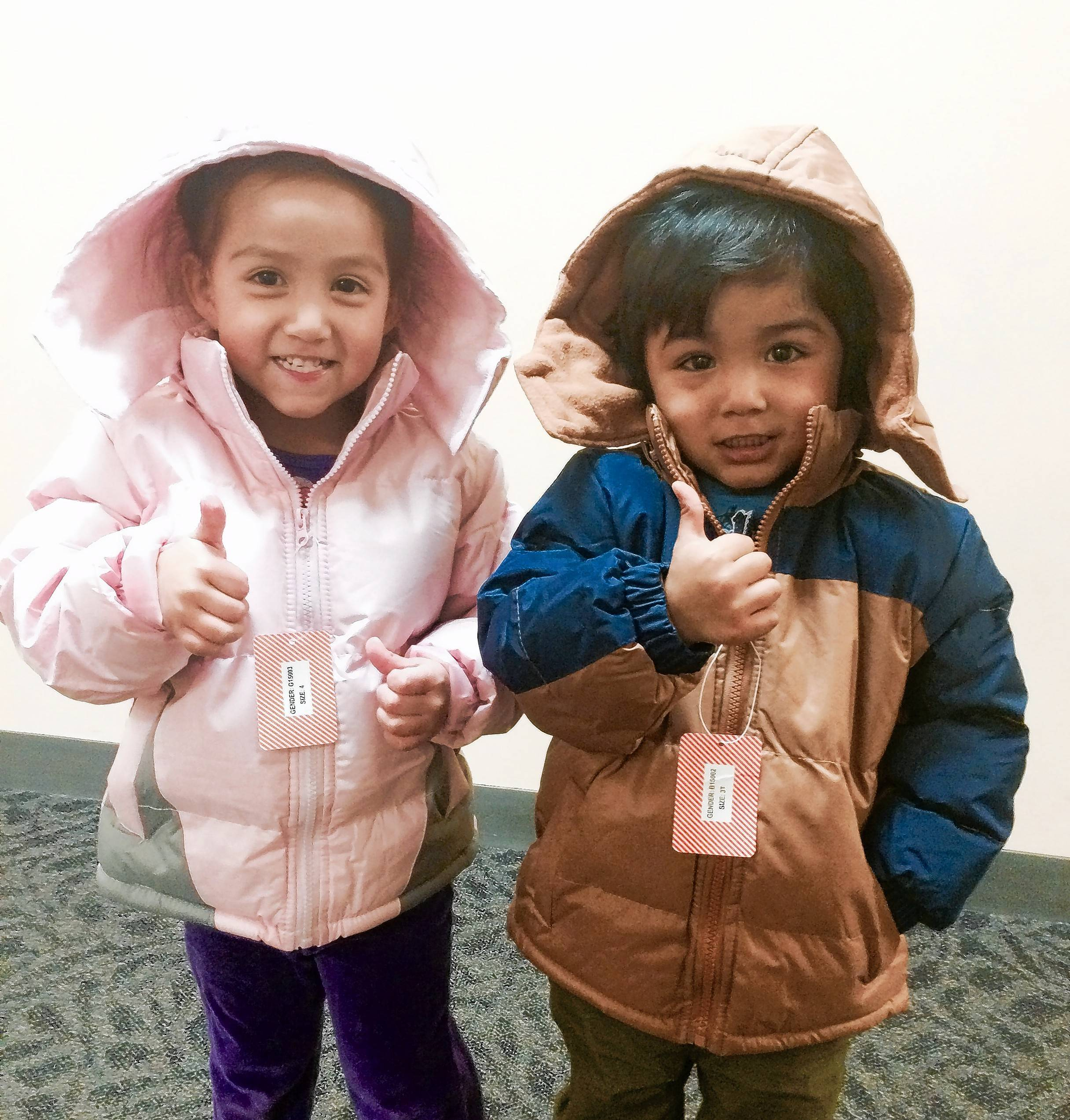 These are two of the recipients of the 400 new coats handed out earlier this month by Woodfield Area Children's Organization secretary Linda McGill as part of the annual New Coats for Kids program.