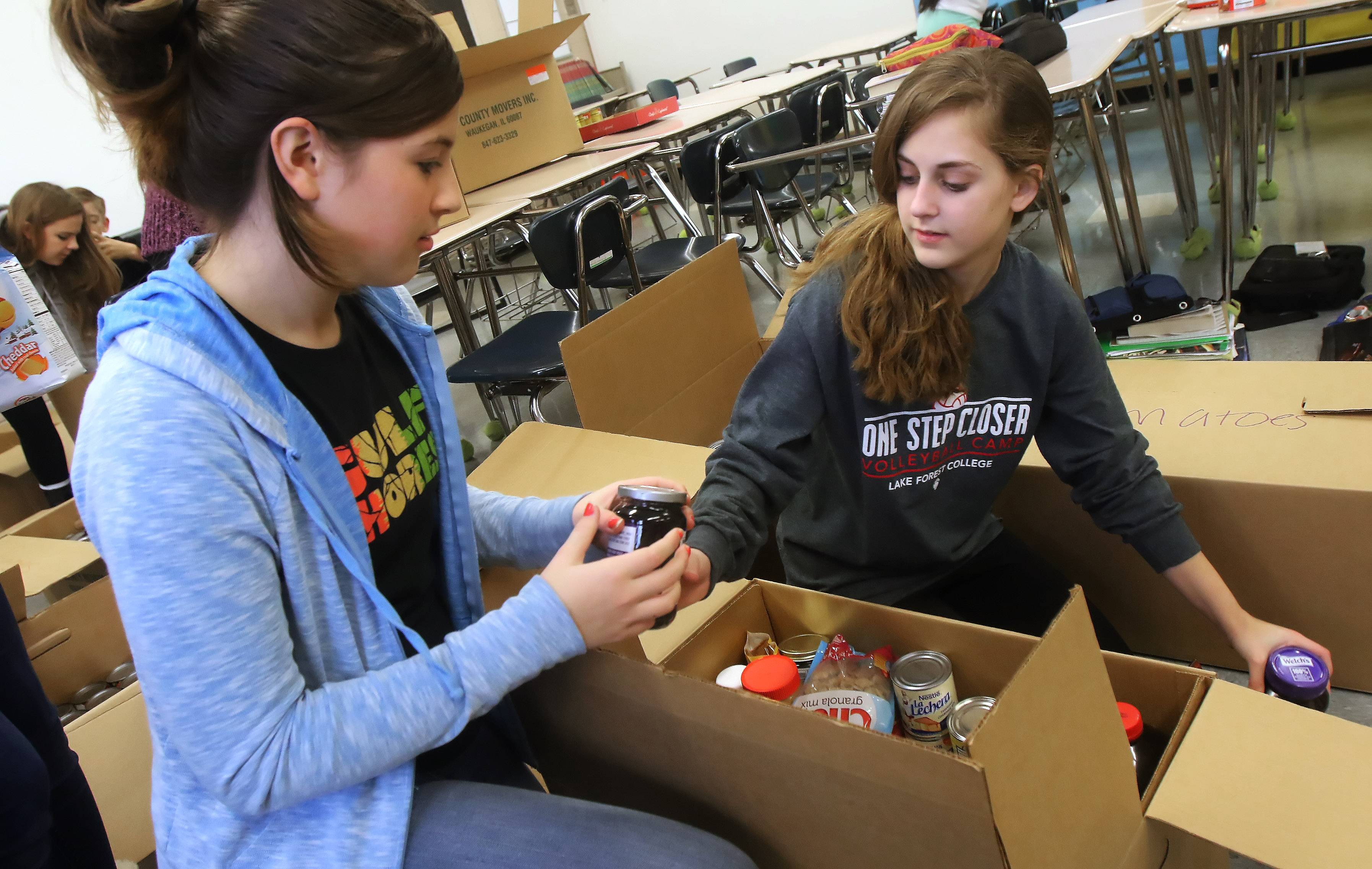 Eighth graders Caitlin Morey, left, and Ella Brandt fill boxes as students from the Junior National Honor Society at Carl Sandburg Middle School in Mundelein pack canned and packaged food Tuesday. The food is being sent to the Fremont Township Food Pantry.