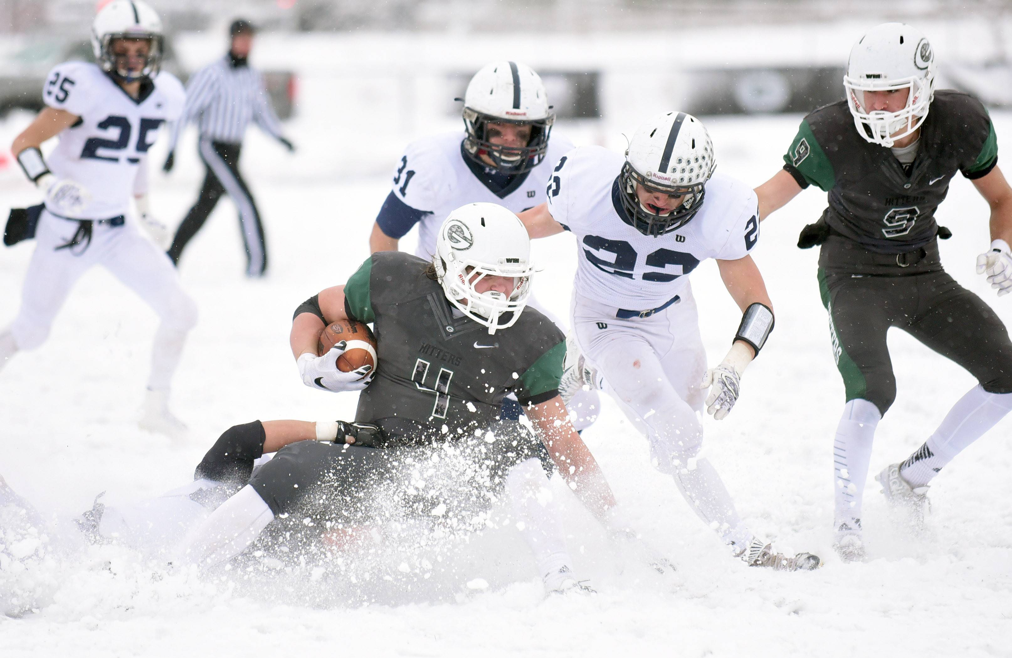 Cary-Grove's Erik Norberg (hidden in the snow spray) takes down Glenbard West's Sam Brodner in the fourth quarter of the Class 7A semifinal at Glenbard South High School in Glen Ellyn Saturday.