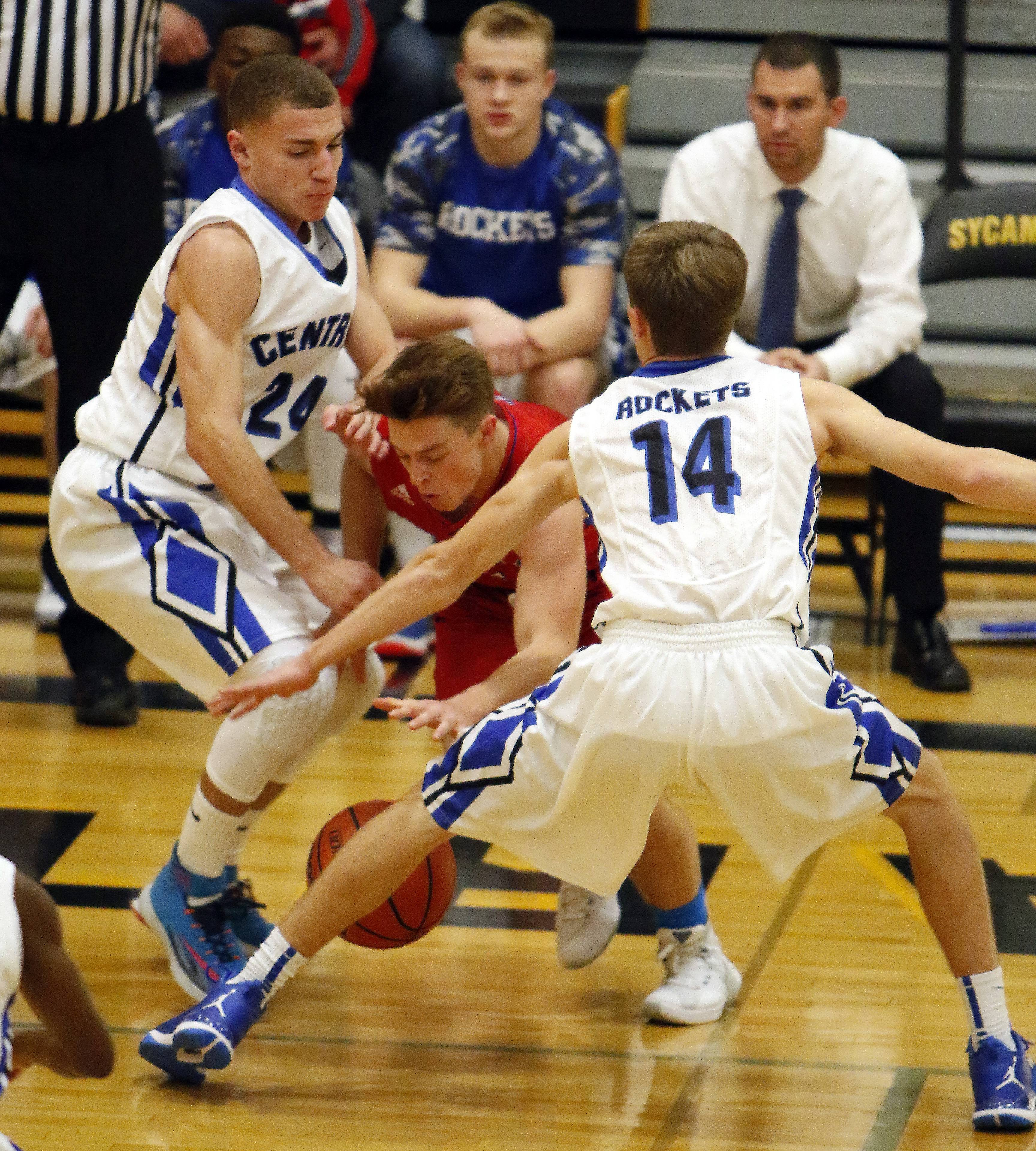 Dundee Crown guard Nicholas Shydlowski (3) tries to squeeze between Burlington Central guards Ethan Mayfield (24) and Zach Schutta (14) during boys basketball at Sycamore Wednesday.