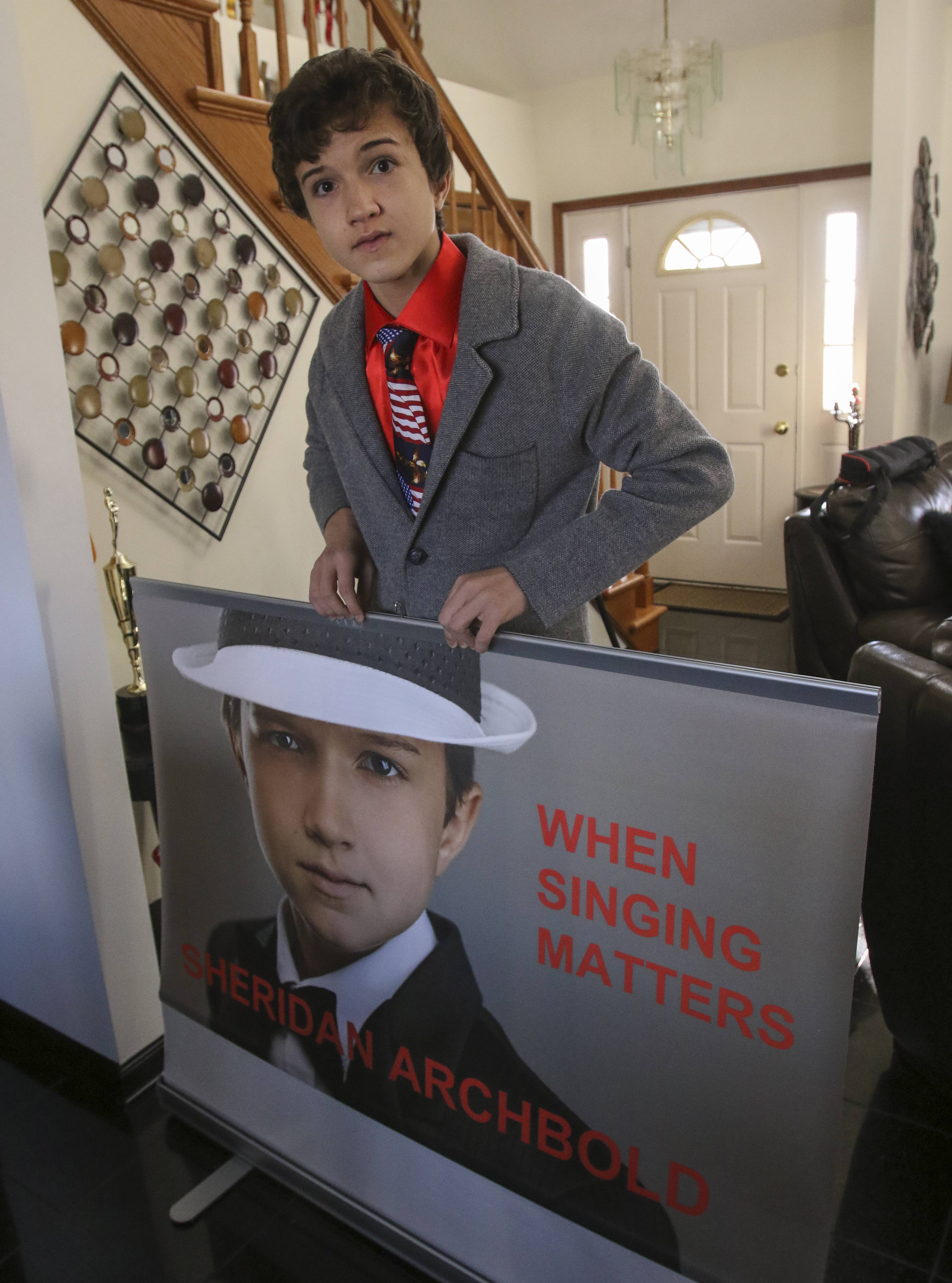 Sheridan Archbold, 14, holds a promotional poster of himself. The young opera singer performed this summer in Italy and is in talks for perform in France in 2017.