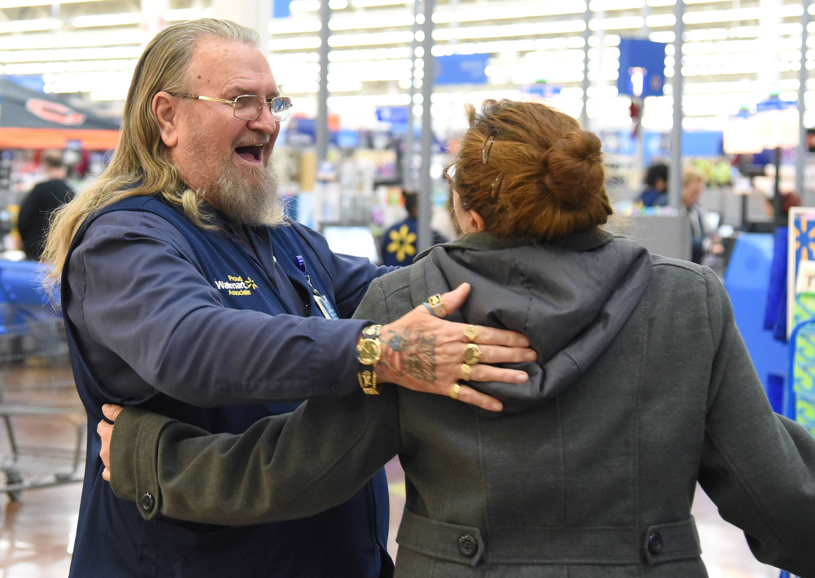 Wal-Mart greeter George Cornwell of Aurora gets a hug from co-worker Eva Reyna, also of Aurora, as she leaves work for the day.