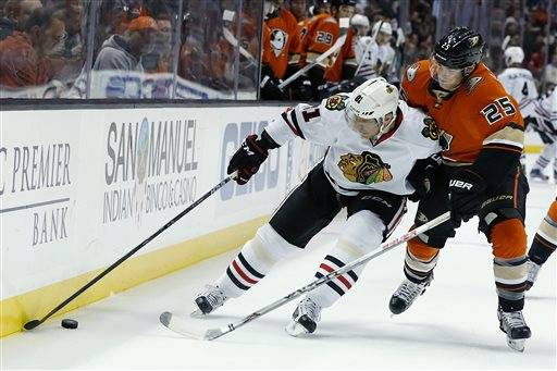 Chicago Blackhawks right wing Marian Hossa, left, battles for control of the puck against Anaheim Ducks center Mike Santorelli (25) in the first period of an NHL hockey game in Anaheim, Calif., Friday, Nov. 27, 2015. (AP Photo/Christine Cotter)
