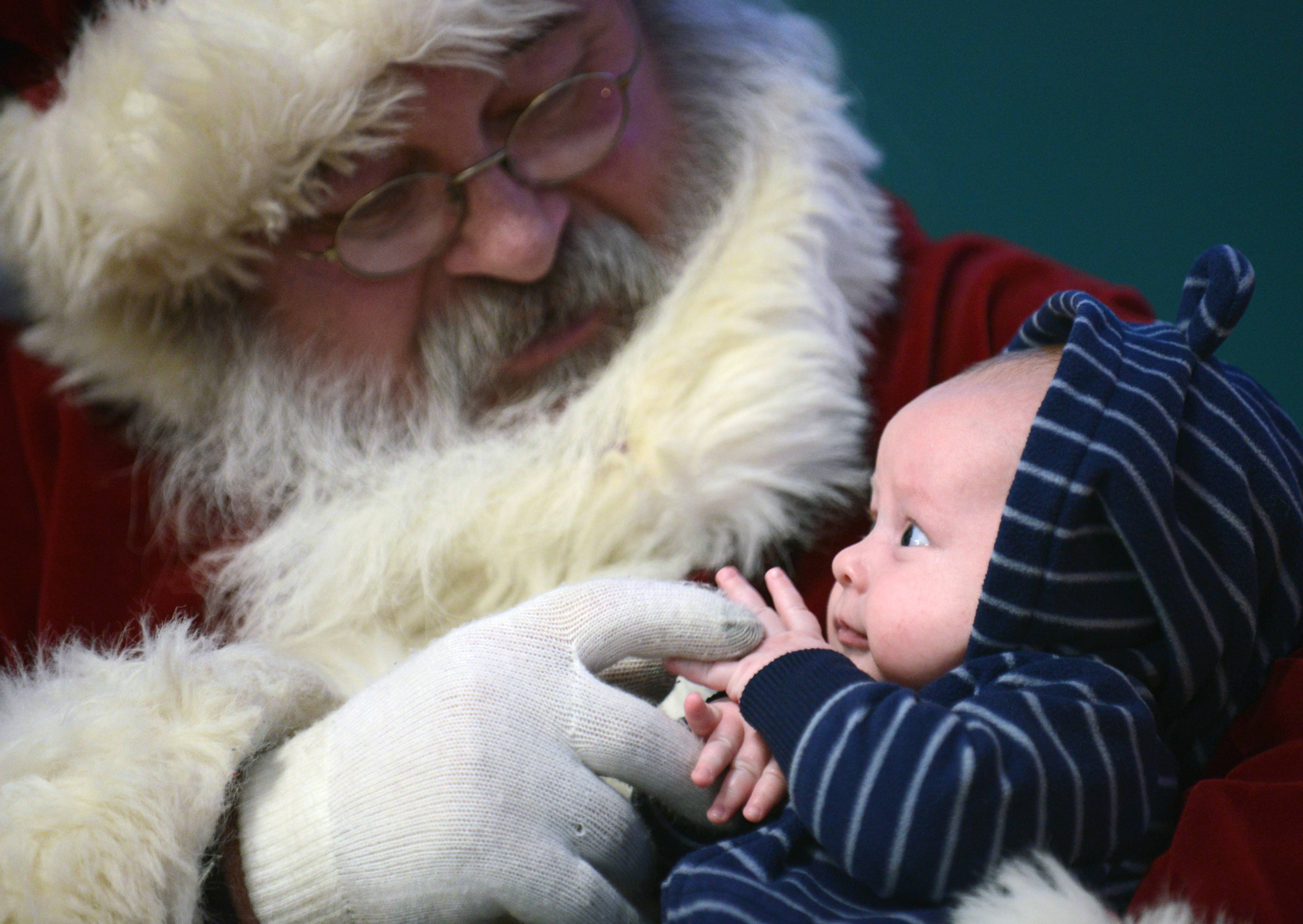 Seven-week-old Smith Potilechio of Elburn gazes up wide-eyed at Santa Claus at the 21st annual Elburn Christmas Stroll Saturday. Moments later, he covered his face with his tiny hands. Smith's older sister, Harlowe, 2, steered clear of the jolly fellow, choosing to stay in her stroller. Kids of all ages waited in line to see Santa at the Town and Country Library.