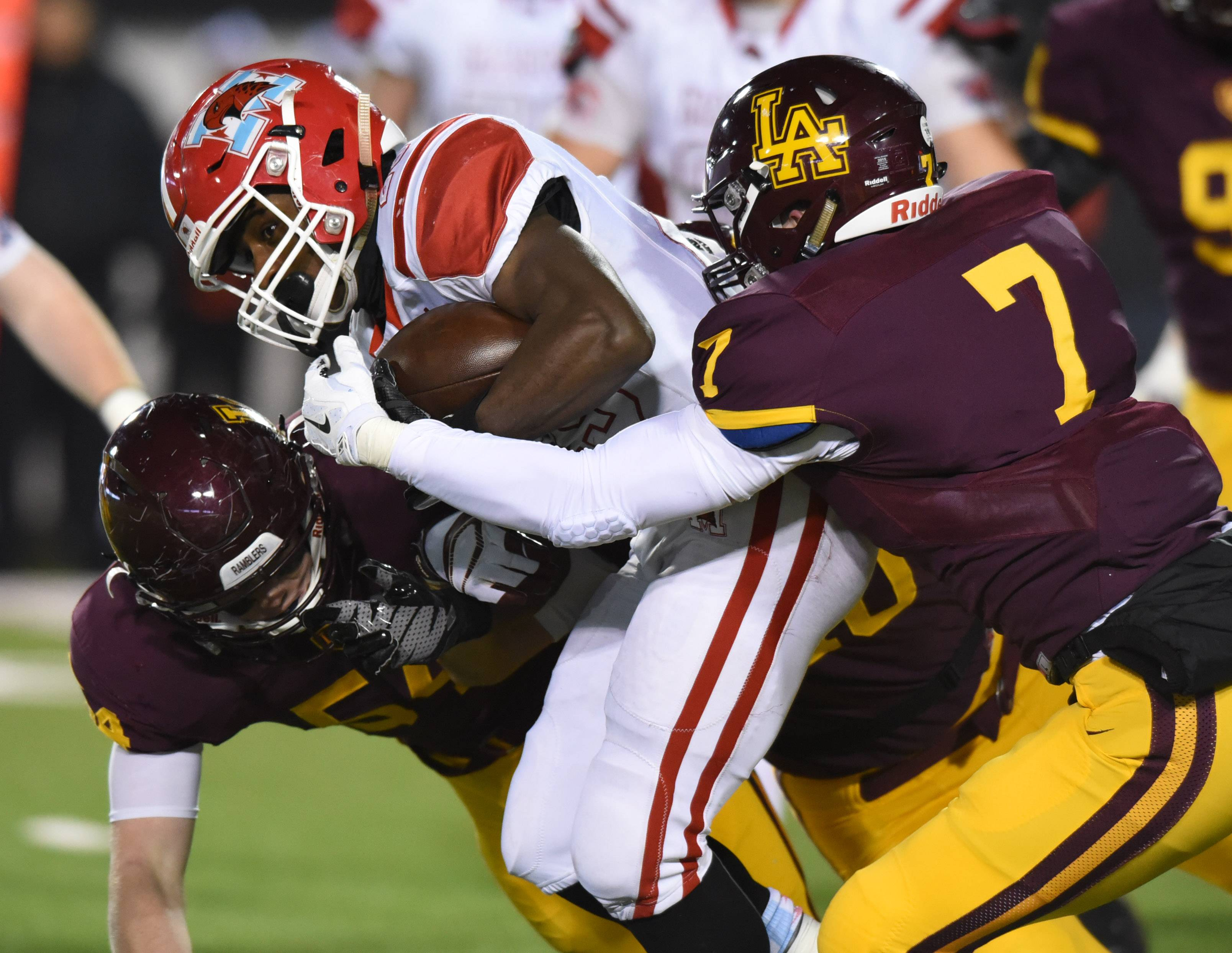 Loyola's Graham Repp, left, and Joey Zitella tackle Marist's Darshon Mccullough during the Class 8A football state final at Huskie Stadium in DeKalb Saturday.