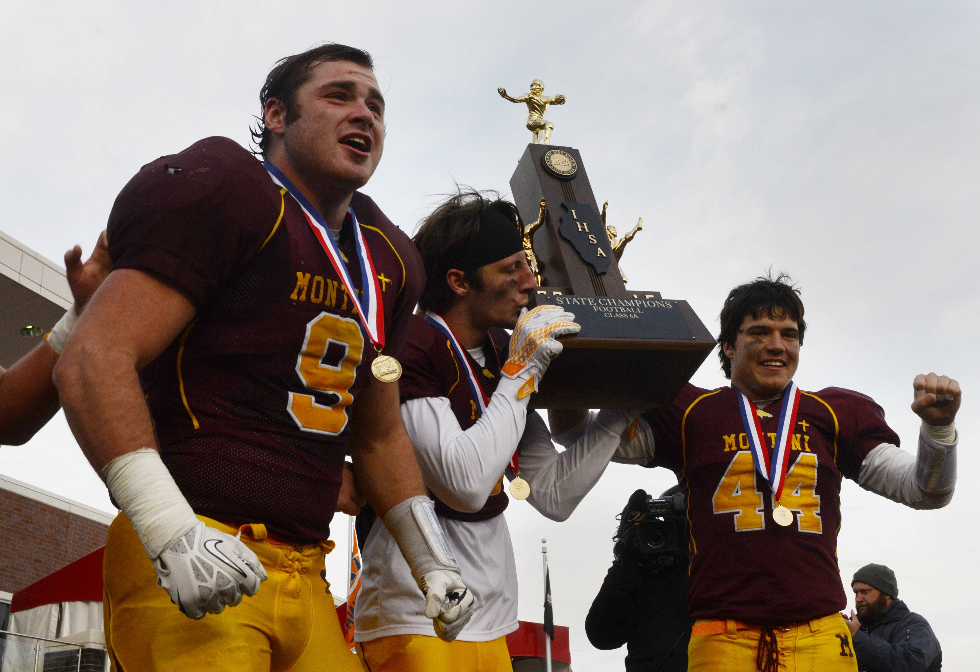 Left to right, Montini's John Embrey, Tyler Millikan and Luke Sheppard celebrate with their team's trophy during the Class 6A football championship game at Northern Illinois University in DeKalb Saturday.