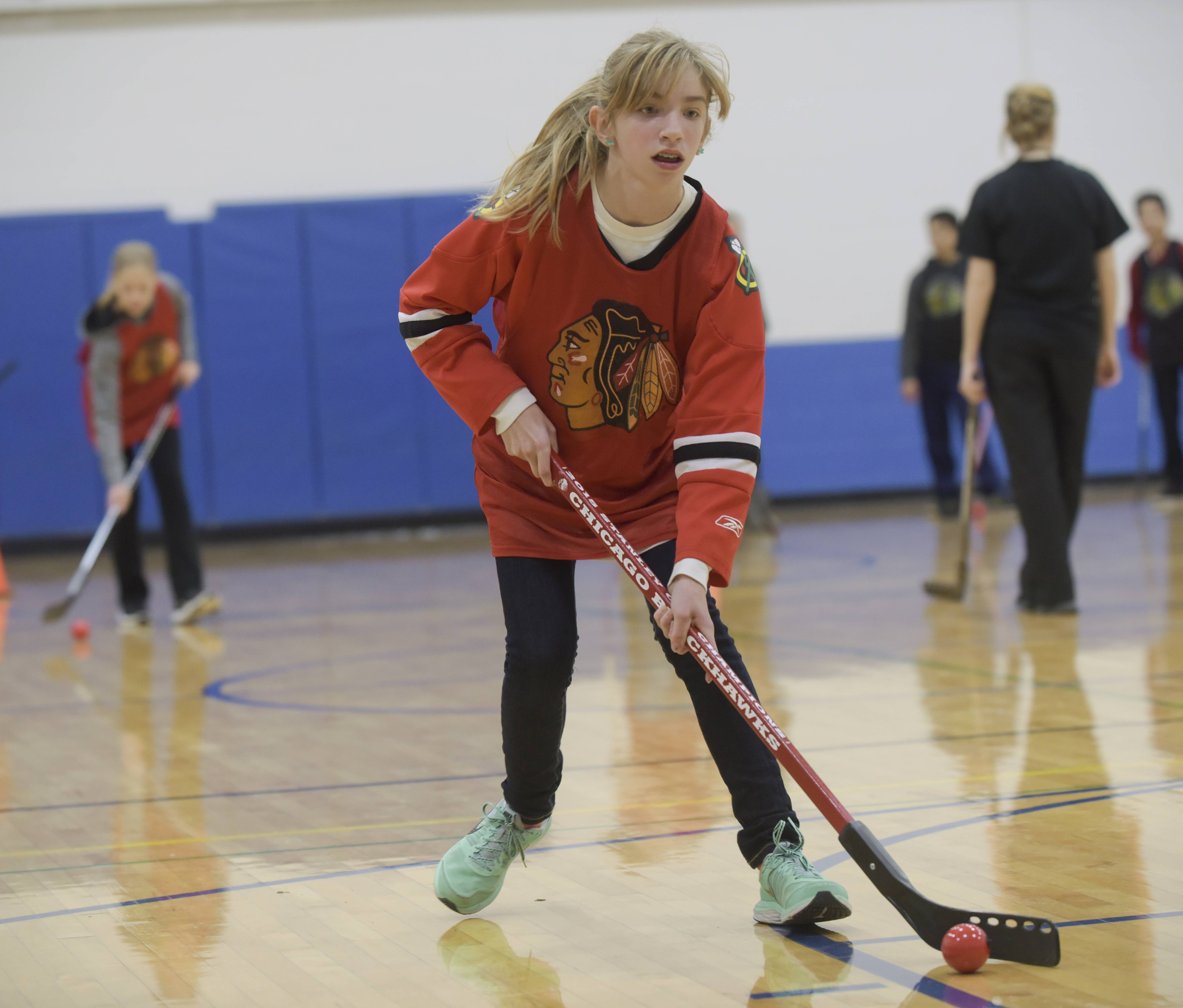 Amber Corrigan, 13, practices some hockey skills during a visit from the Chicago Blackhawks' fan development team Monday at Glenn Westlake Middle School in Lombard.
