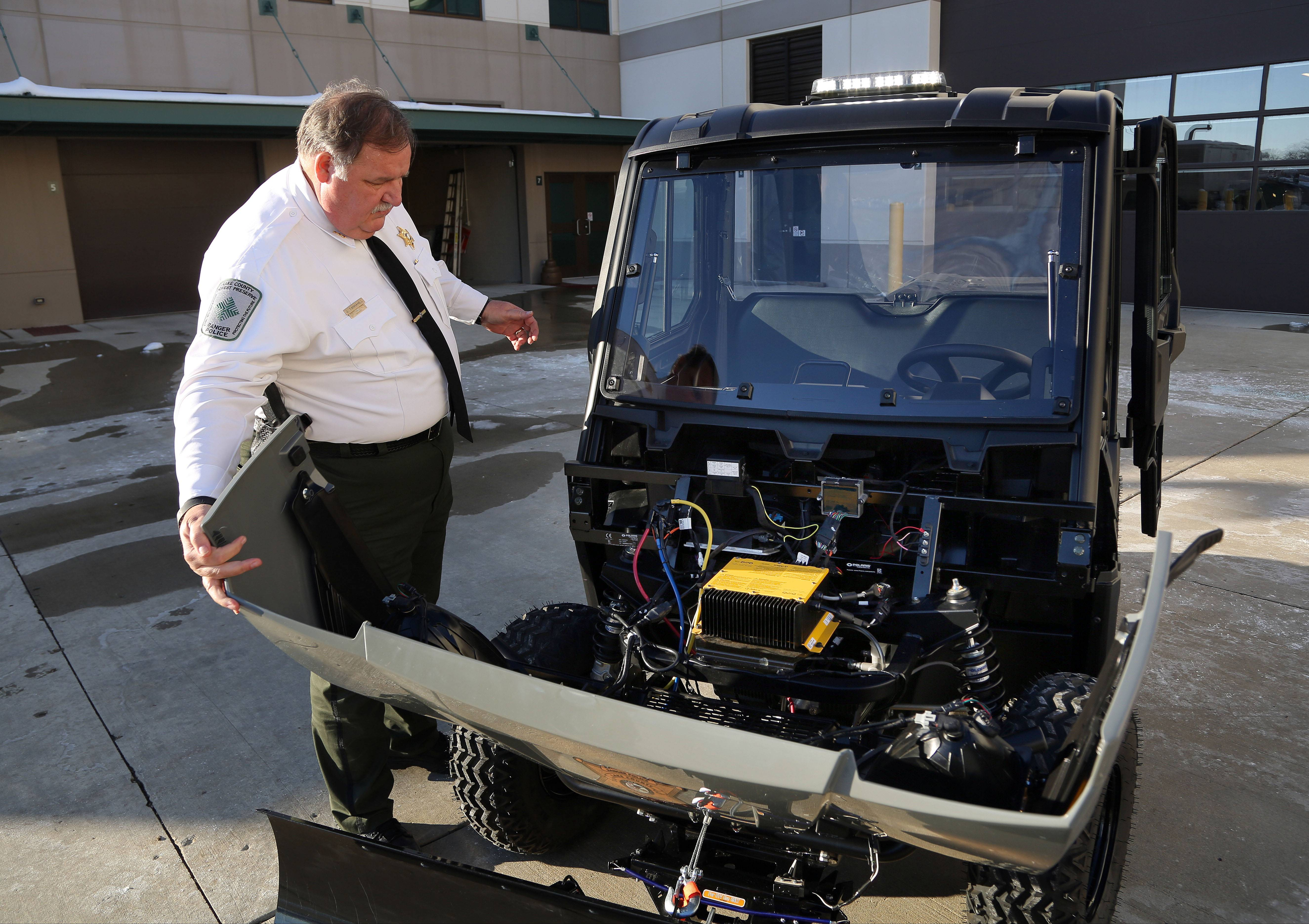 Lake County Forest Preserve District Director of Public Safety John Tannahill opens the hood of their new all-electric Polaris Ranger 4x4.
