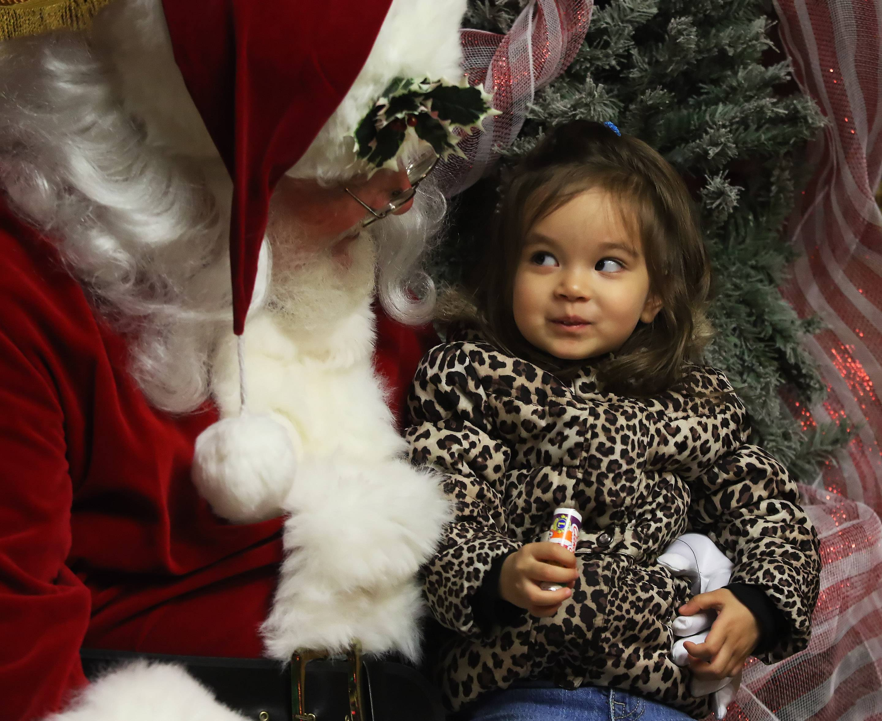 "Two-year-old Umeno Tekampe of Mundelein talks to Santa Claus, Alan Bidnar, at Santa's Frozen Village in Antioch on Sunday. Children and families met with Santa Claus and characters from the Disney movie ""Frozen"" at the downtown site."