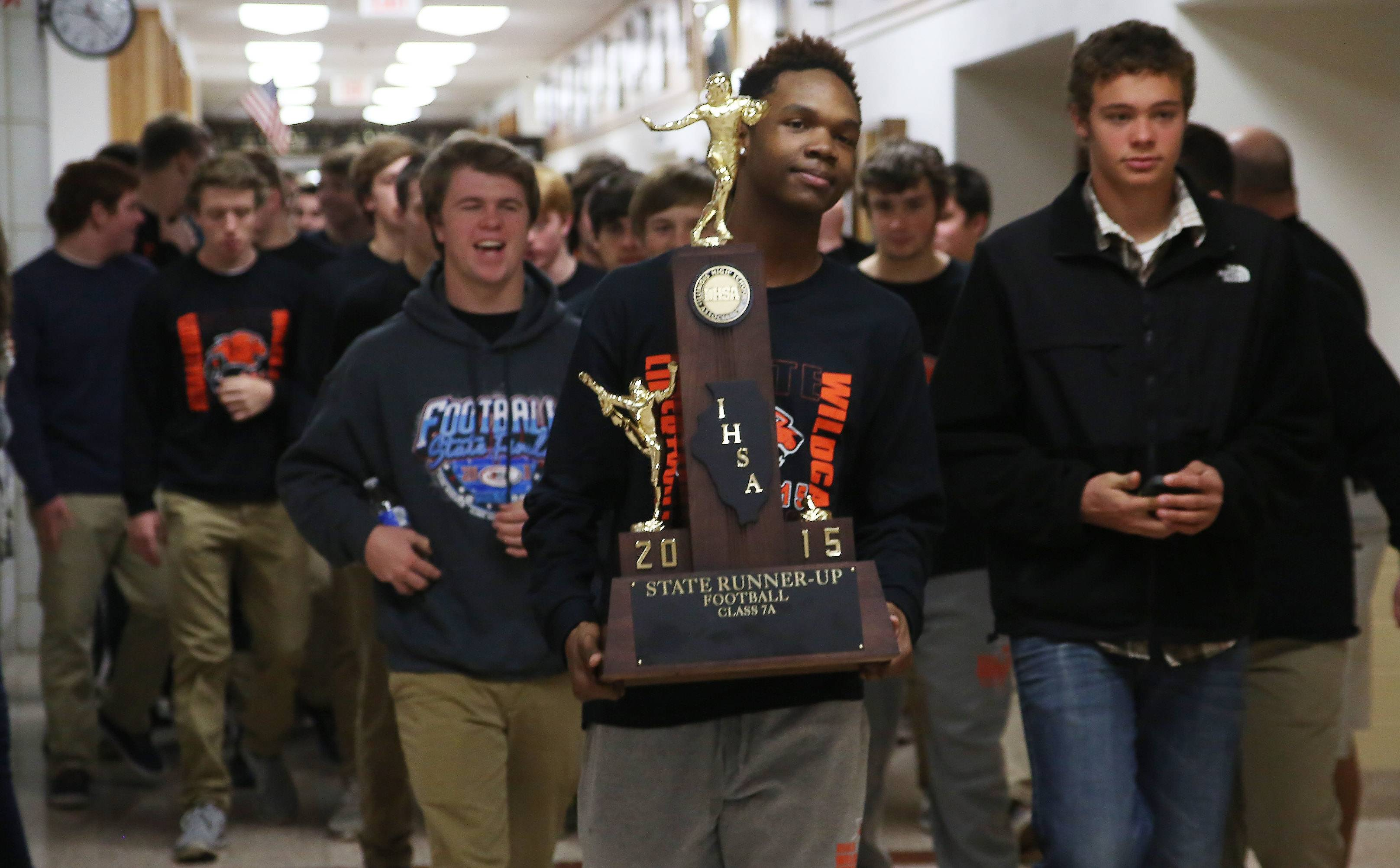Libertyville High School wide receiver Carl Heard carries the IHSA Class 7A state championship runner-up trophy as the football team is cheered while parading through the school Monday. The team finished the season with a 13-1 record.