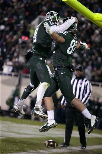 Michigan State quarterback Connor Cook, left, and tight end Josiah Price celebrate Price's touchdown reception against Penn State during the third quarter of an NCAA college football game, Saturday, Nov. 28, 2015, in East Lansing, Mich. Michigan State won 55-16. (AP Photo/Al Goldis)