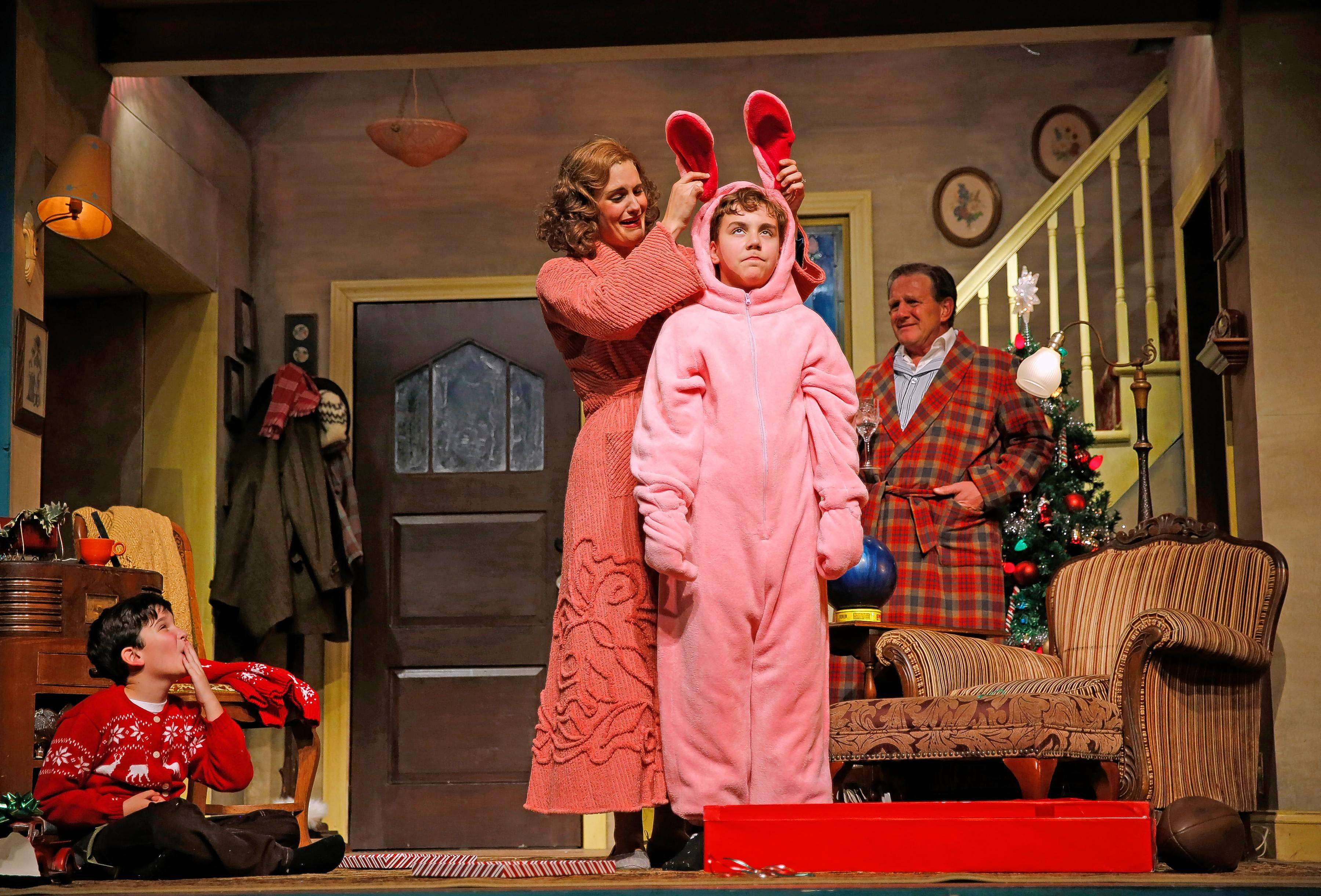 "Christmas morning isn't exactly what Ralphie (Michael Harp, in bunny suit) expected in ""A Christmas Story — The Musical,"" adapted from humorist Jean Shepherd's memoirs and Bob Clark's 1983 film. Theo Moss, left, plays younger brother Randy, Danni Smith plays the mother and Michael Accardo plays the Old Man in Paramount Theatre's revival directed by Nick Bowling."