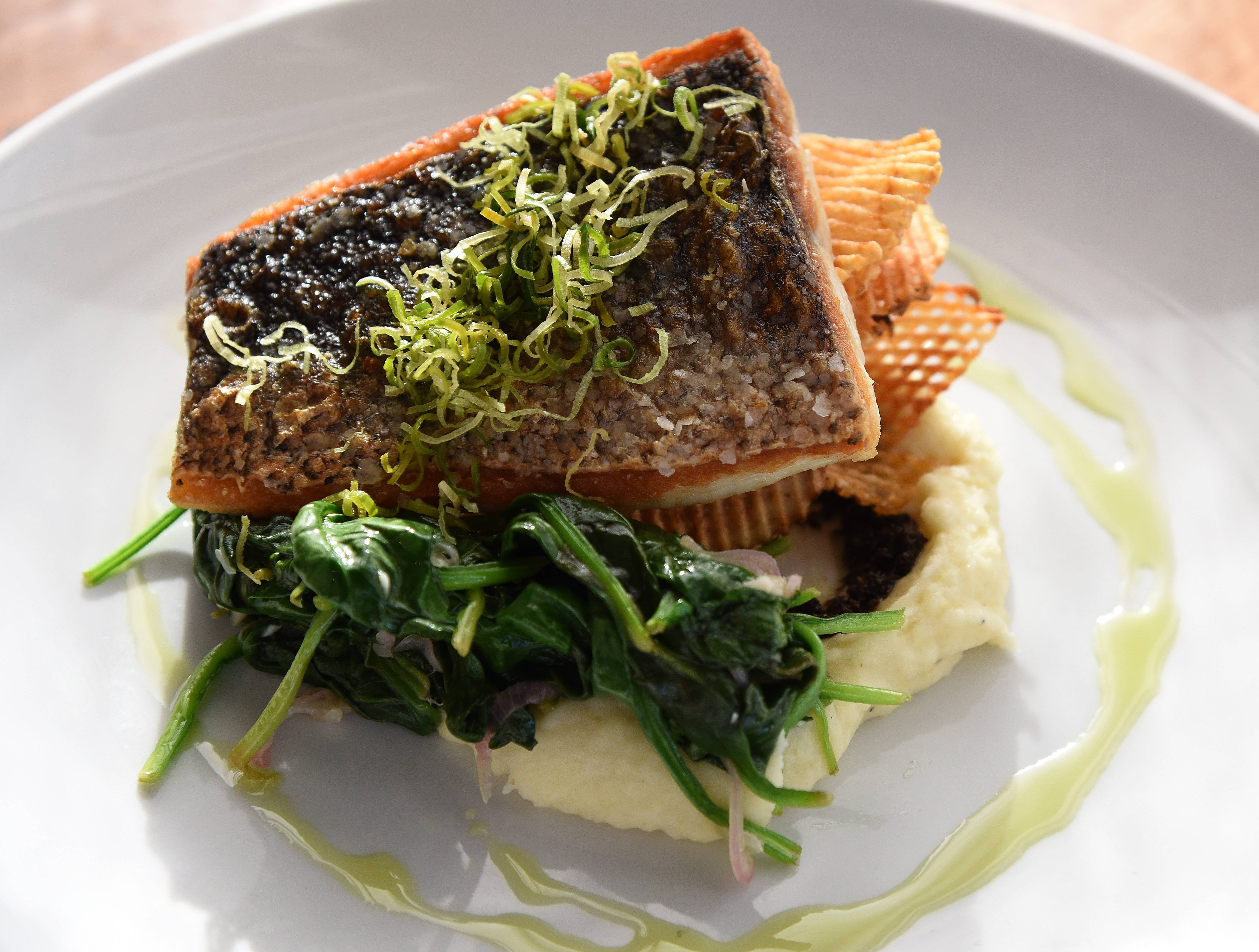The perfectly seasoned pan-seared black sea bass is accompanied by a leek-potato puree, sauteed spinach and homemade waffle chips at The Finery.