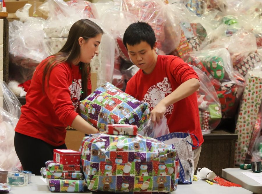 Stevenson High School National Honor Society members Melisa Dove, left, and Eric Ren fill bags with presents Tuesday during the 31st annual Give-A-Thon at the Lincolnshire school. School students and staff are providing holiday gifts for 320 Lake County families, stocking the Vernon Township Food Pantry and giving baby items to Lake County PADS.