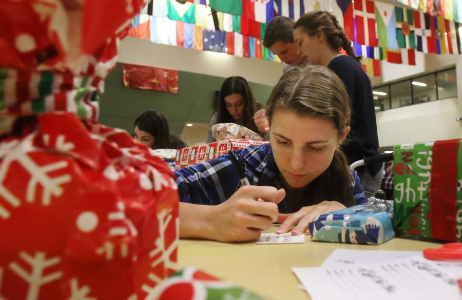 Stevenson High School Junior Michaela Faunce fills out a name tag for a present Tuesday during the 31st annual Give-A-Thon at the Lincolnshire school. School students and staff are providing for 320 holiday gifts for Lake County families, stocking the Vernon Township Food Pantry and giving baby items to Lake County PADS.