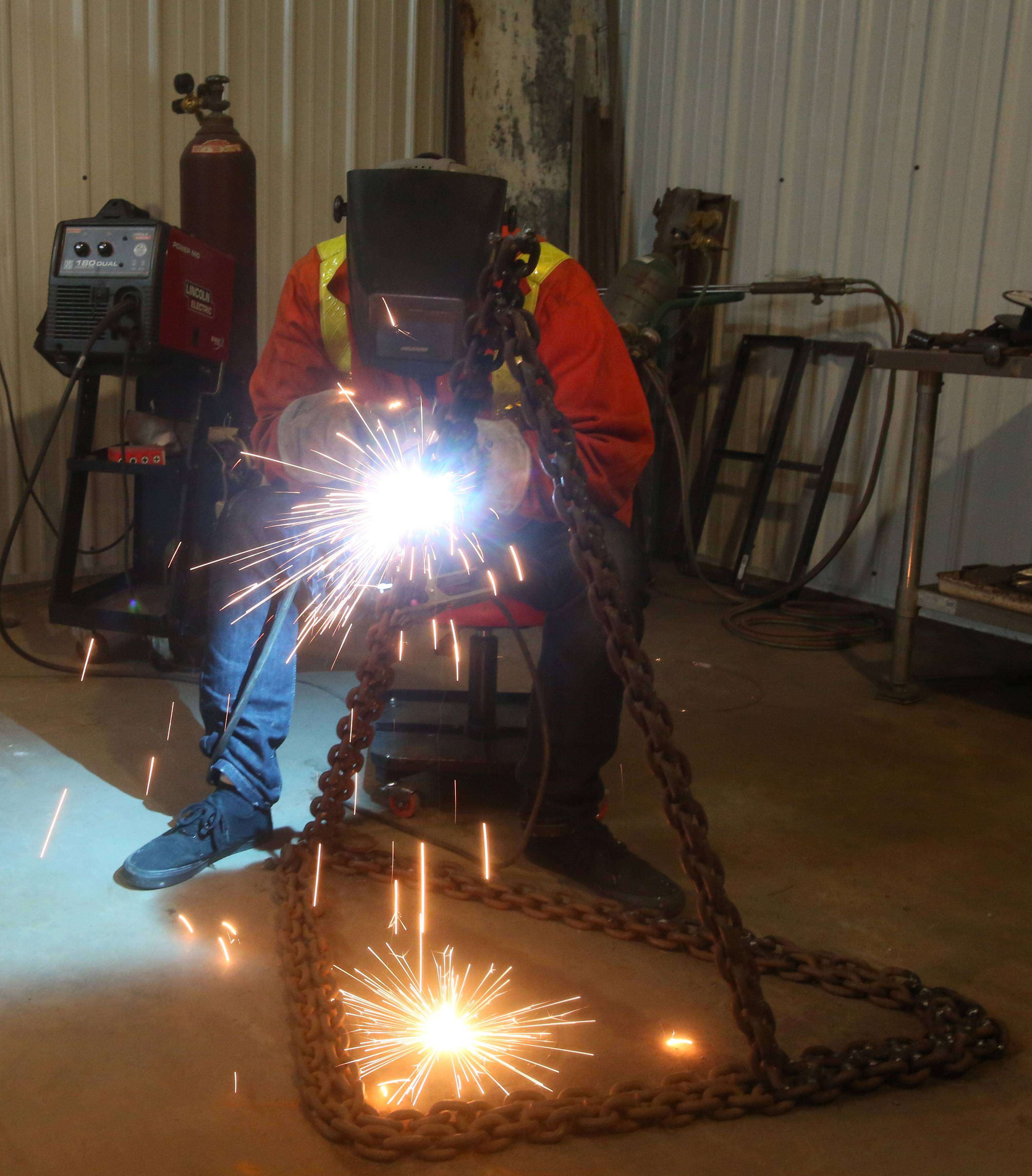 Naperville artist Paul Kuhn welds recycled chain into a base for a future project.