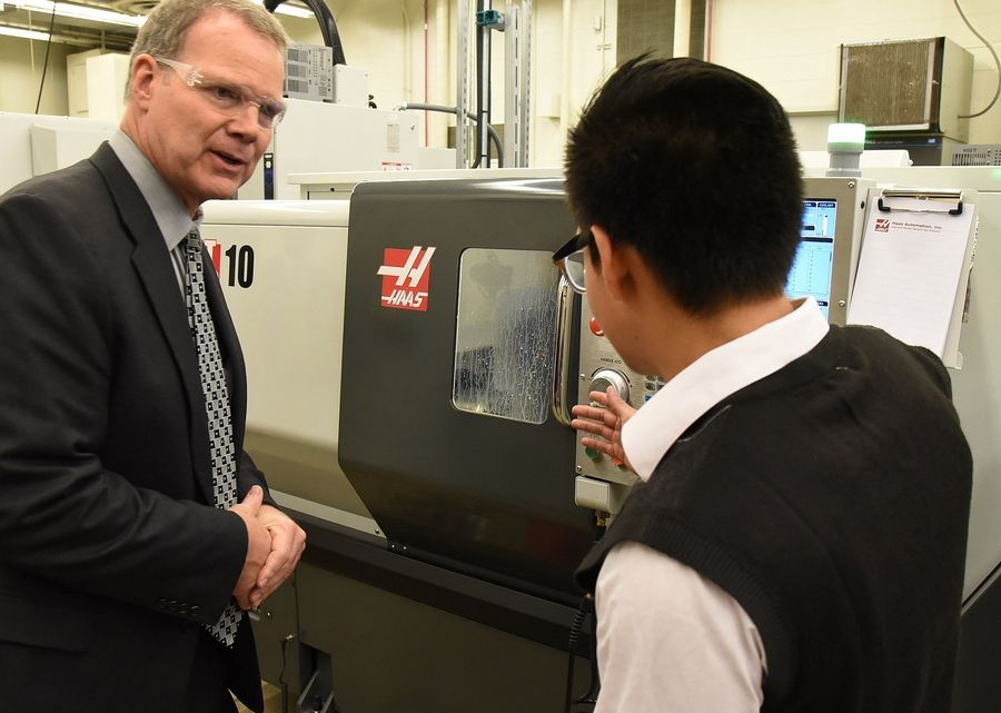Junior Luis Miranda demonstrates a CNC Lathe in his Advanced Manufacturing Technology class to Illinois State Superintendent Tony Smith during a tour Thursday of District 211's STEM program at Palatine High School.
