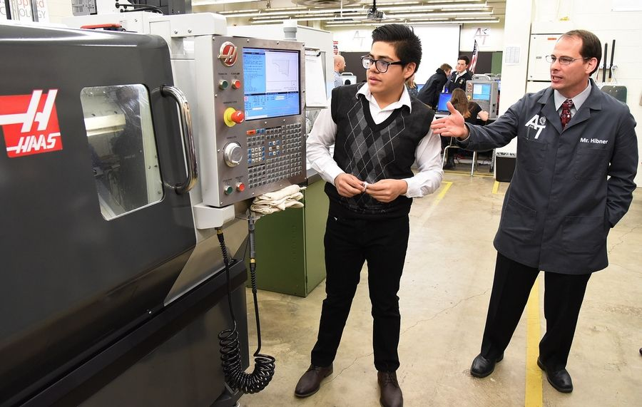 Junior Luis Miranda and Advanced Manufacturing instructor Mark Hibner prepare to demonstrate a CNC Lathe in an Advanced Manufacturing Technology class to Illinois State Superintendent Tony Smith and educators during a tour Thursday of District 211's STEM program at Palatine High School.