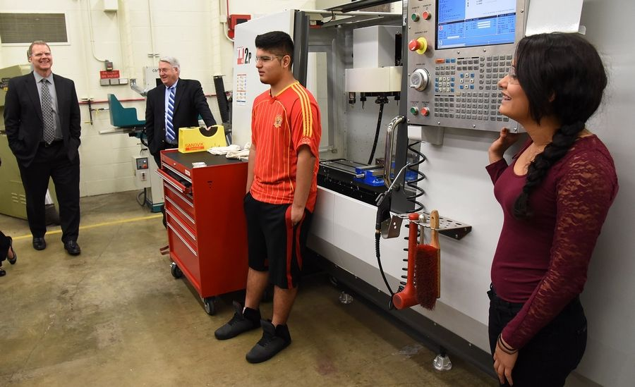 Sophomores Sergio Guzman and Melanie Castillo demonstrate a CNC Mill in their Advanced Manufacturing Technology class to Illinois State Superintendent Tony Smith, left, and educators during a tour of District 211's STEM program at Palatine High School.
