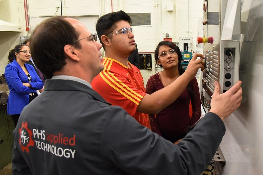 Advanced Manufacturing instructor Mark Hibner and sophomores Sergio Guzman and Melanie Castillo demonstrate a CNC Mill in their Advanced Manufacturing Technology class to Illinois State Superintendent Tony Smith, left, and educators at Palatine High School.