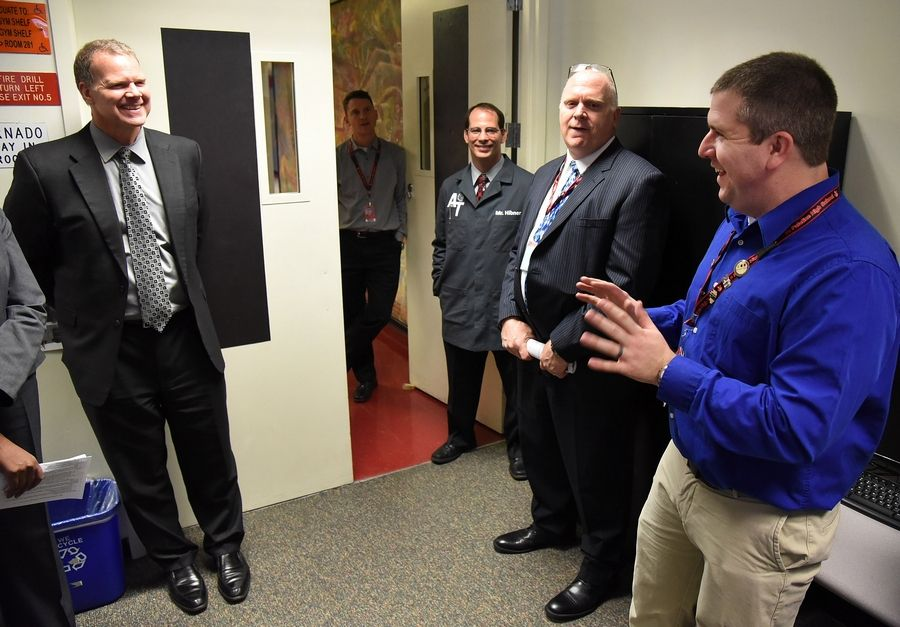Project Lead the Way instructor Alex Larson, right, explains the STEM R&D program to Illinois State Superintendent Tony Smith, left, and educators during a tour of District 211's STEM program at Palatine High School.