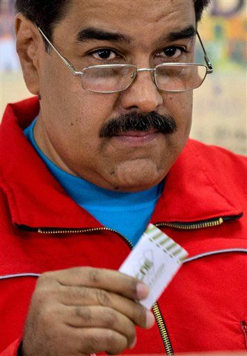 "Venezuela's President Nicolas Maduro holds up his electronic voting receipt before placing it in a box during congressional elections in Caracas, Venezuela, Sunday, Dec. 6, 2015. Maduro had repeatedly vowed in recent weeks to take to the streets if his party lost. But the president changed his tone on Saturday, saying: ""In Venezuela, peace and democracy must reign. I've said we'll take the fight to the streets, but maybe I was wrong."""