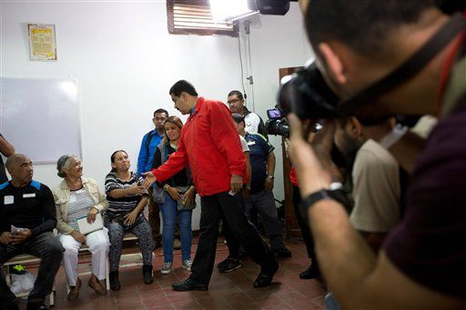 Venezuela's President Nicolas Maduro greets electoral workers as he arrives to vote in congressional elections in Caracas, Venezuela, Sunday, Dec. 6, 2015.
