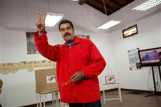 Venezuela's President Nicolas Maduro flashes a victory sign before voting during congressional elections in Caracas, Venezuela, Sunday, Dec. 6, 2015.