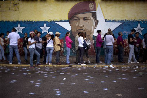 A mural of Venezuelan's late President Hugo Chavez decorates a wall outside a polling station where voters wait to enter during congressional elections in Caracas, Venezuela, Sunday, Dec. 6, 2015. The system built by Chavez faces its gravest electoral test as voters cast ballots in what seems to have become a tightening race for control of the national legislature.