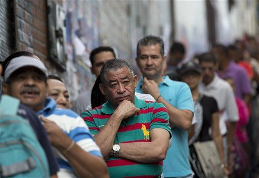 Voters wait in line to enter a polling station during congressional elections in Caracas, Venezuela, Sunday, Dec. 6, 2015.