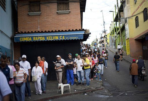 Voters wait in line outside a polling station during congressional elections in Caracas, Venezuela, Sunday, Dec. 6, 2015.