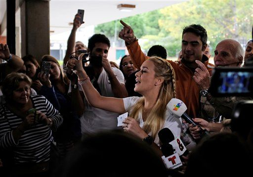 Lilian Tintori, the wife of jailed opposition leader Leopoldo Lopez, gives a thumbs up as she arrives to a polling station during congressional elections in Caracas, Venezuela, Sunday, Dec. 6, 2015. Polls show the opposition coalition holding a 30 point lead.