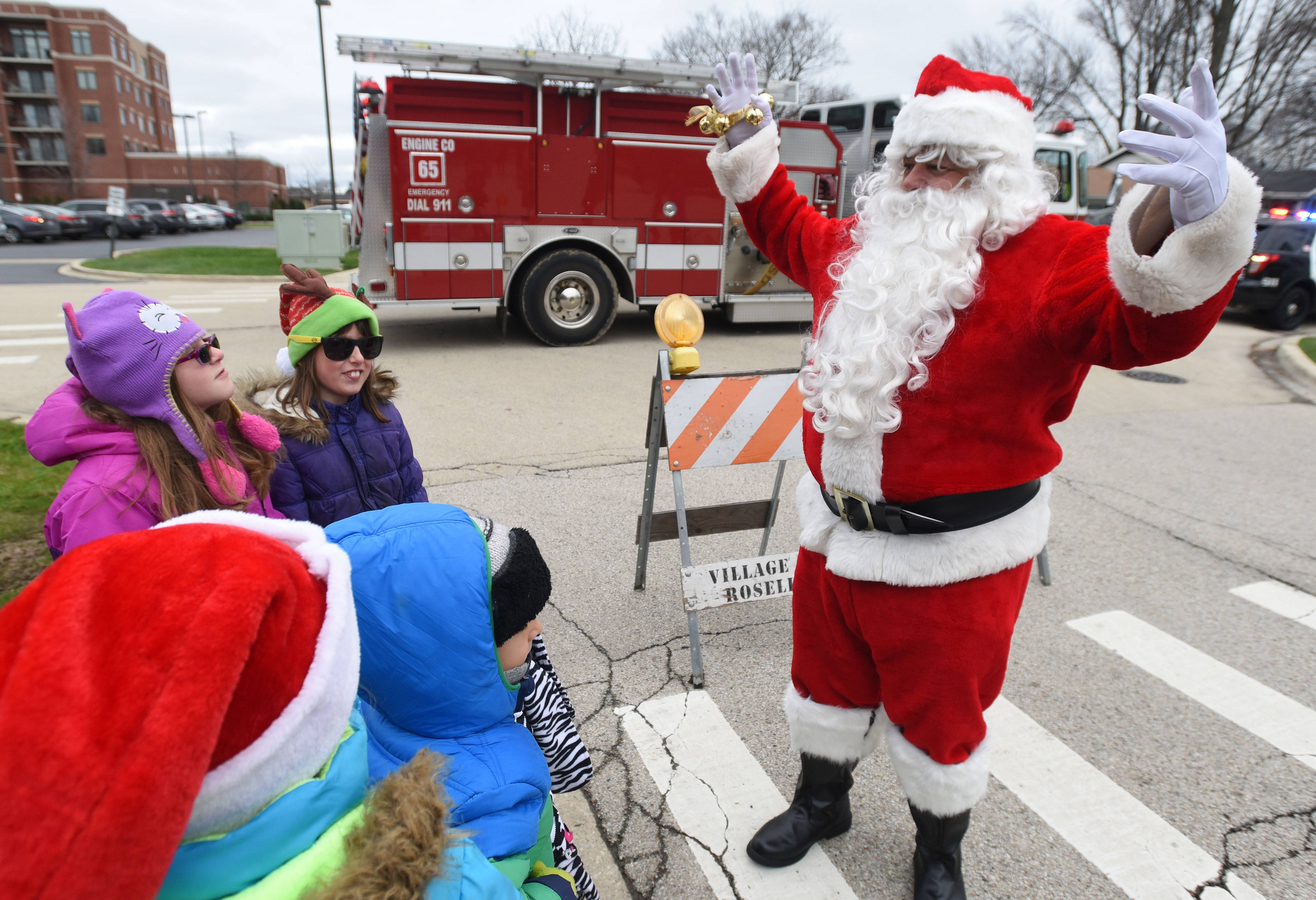 "Santa sings ""Jingle Bells"" for a group of young fans during the holiday festival and tree-lighting at the Roselle Public Library Saturday. More than 60 people sang along."