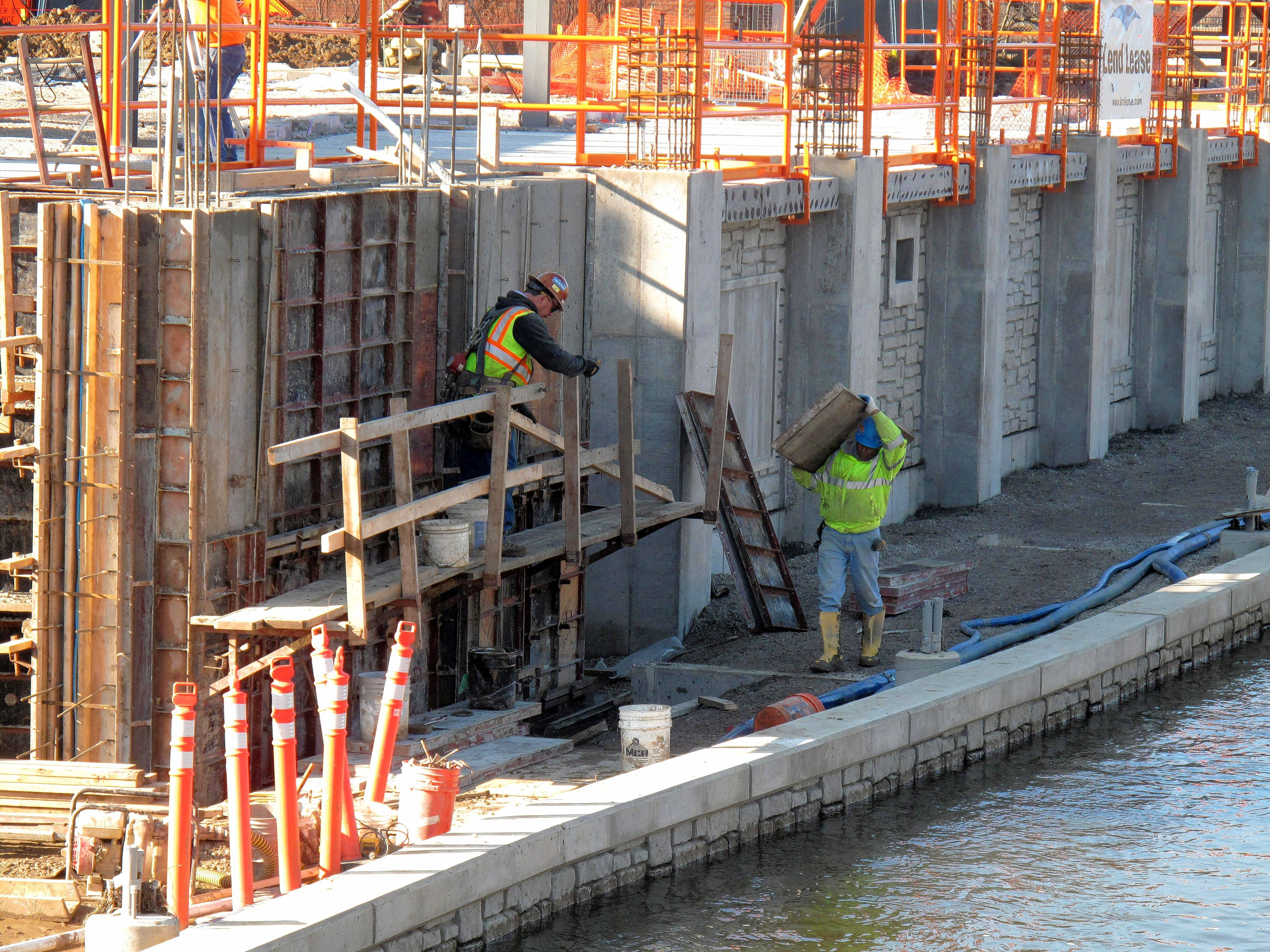 Construction crews work on the boardwalk wall along the Riverwalk at the Water Street District in downtown Naperville.