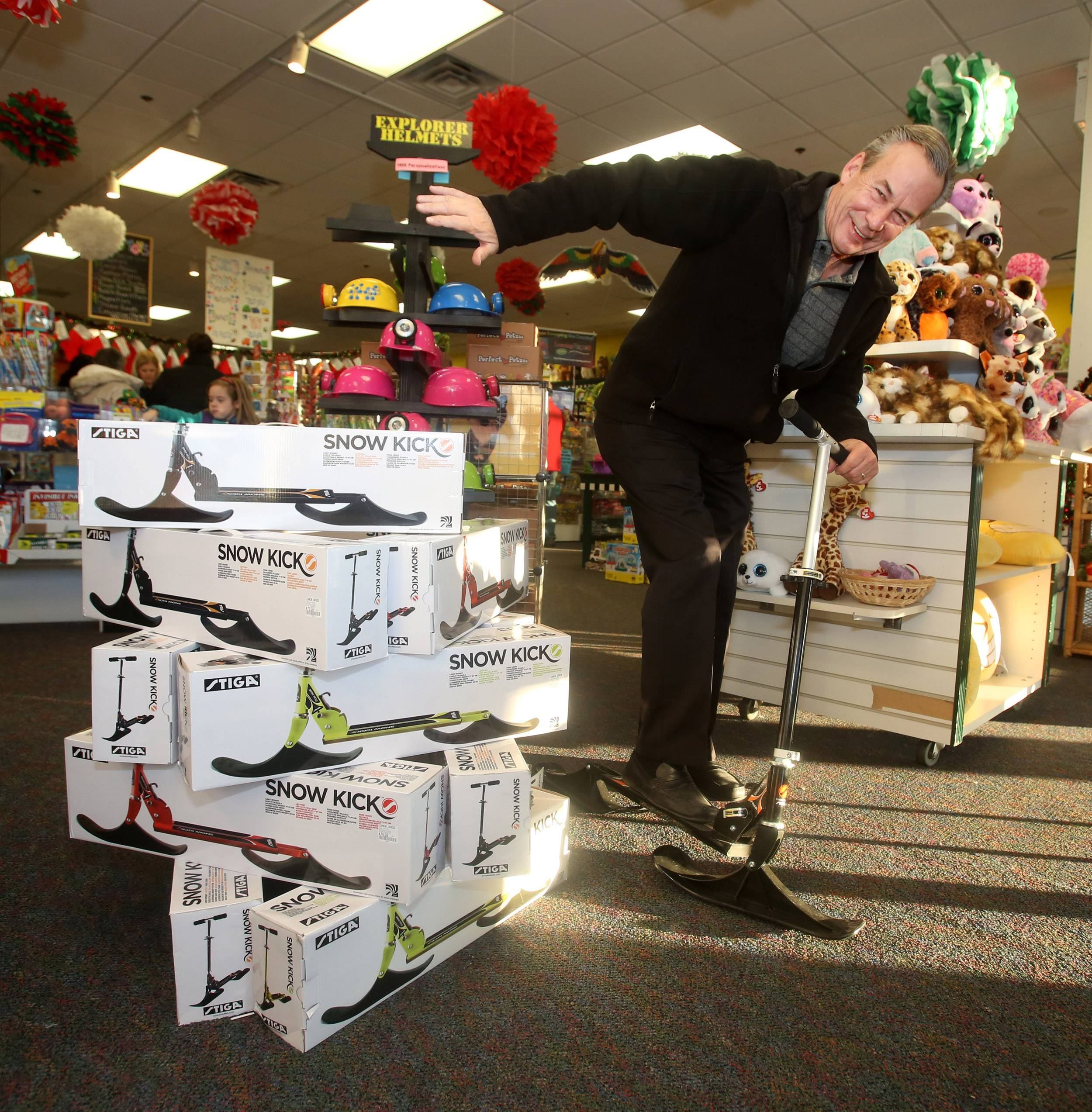 Learning Express store owner Steve Zdunek displays a Snow Kick scooter with skis, popular at his Naperville store.