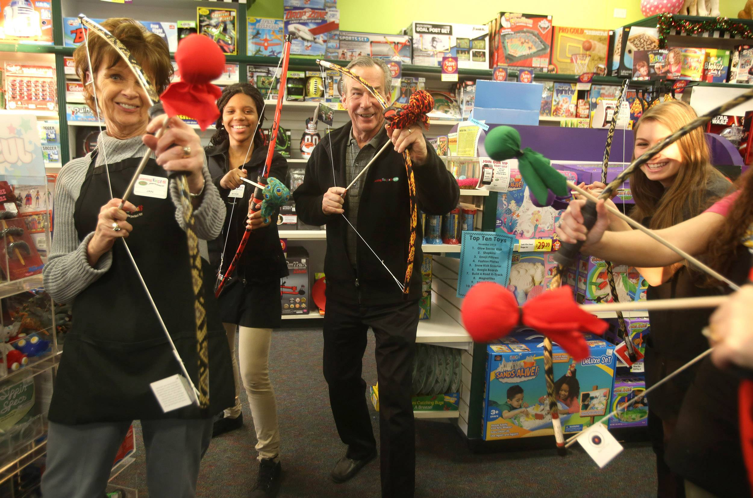 Learning Express store employees led by owner Steve Zdunek, center, pose for a photo with Two Bros Bows, with bows and arrows that have beanbag tips, at his store in Naperville.