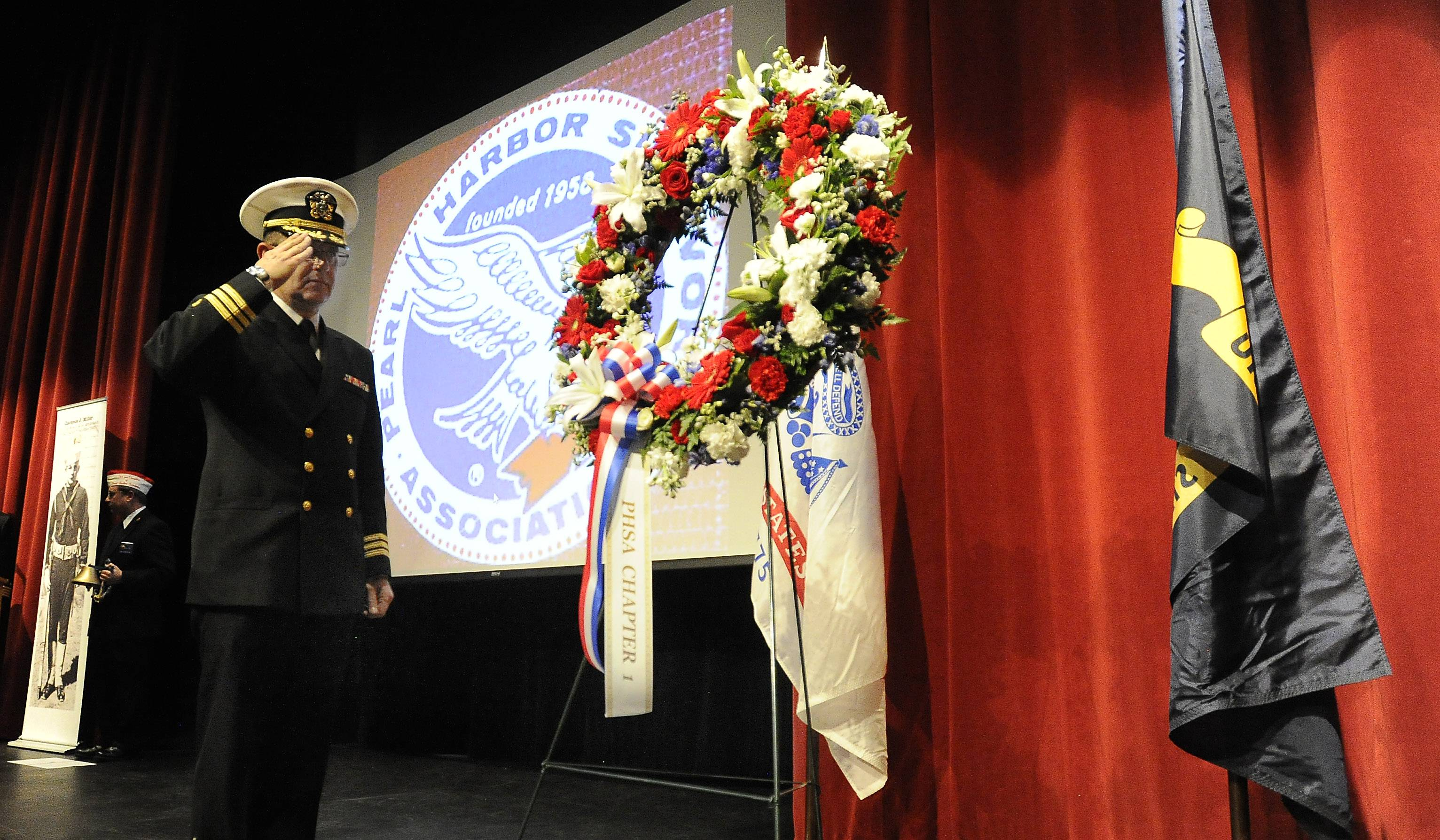 Commander Waldemar Kilian, a chaplain at Naval Station Great Lakes near North Chicago, salutes during a wreath presentation at a Pearl Harbor Remembrance Day ceremony Monday in Des Plaines.