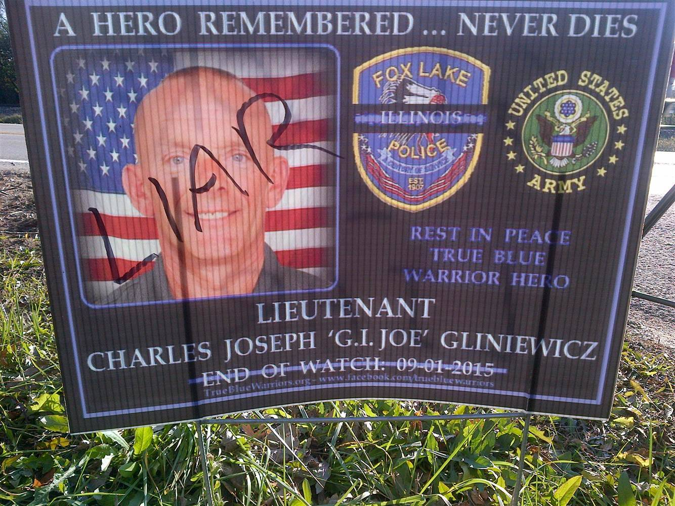 "A sign once honoring Fox Lake Police Lt. Joseph Gliniewicz is defaced with the word ""liar"" after it was determined his death was a suicide staged to look like murder."
