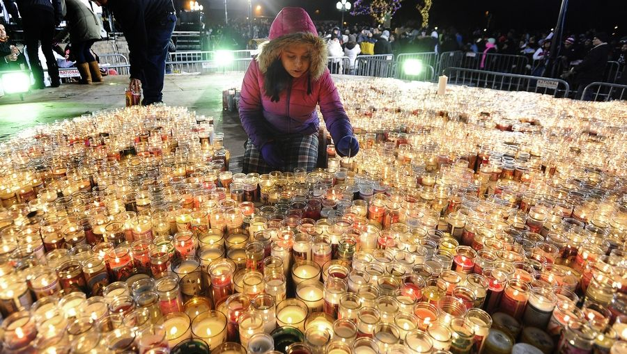 Kassandra Jamie, 12, of Streamwood lights candles at celebration honoring Our Lady of Guadalupe last year.